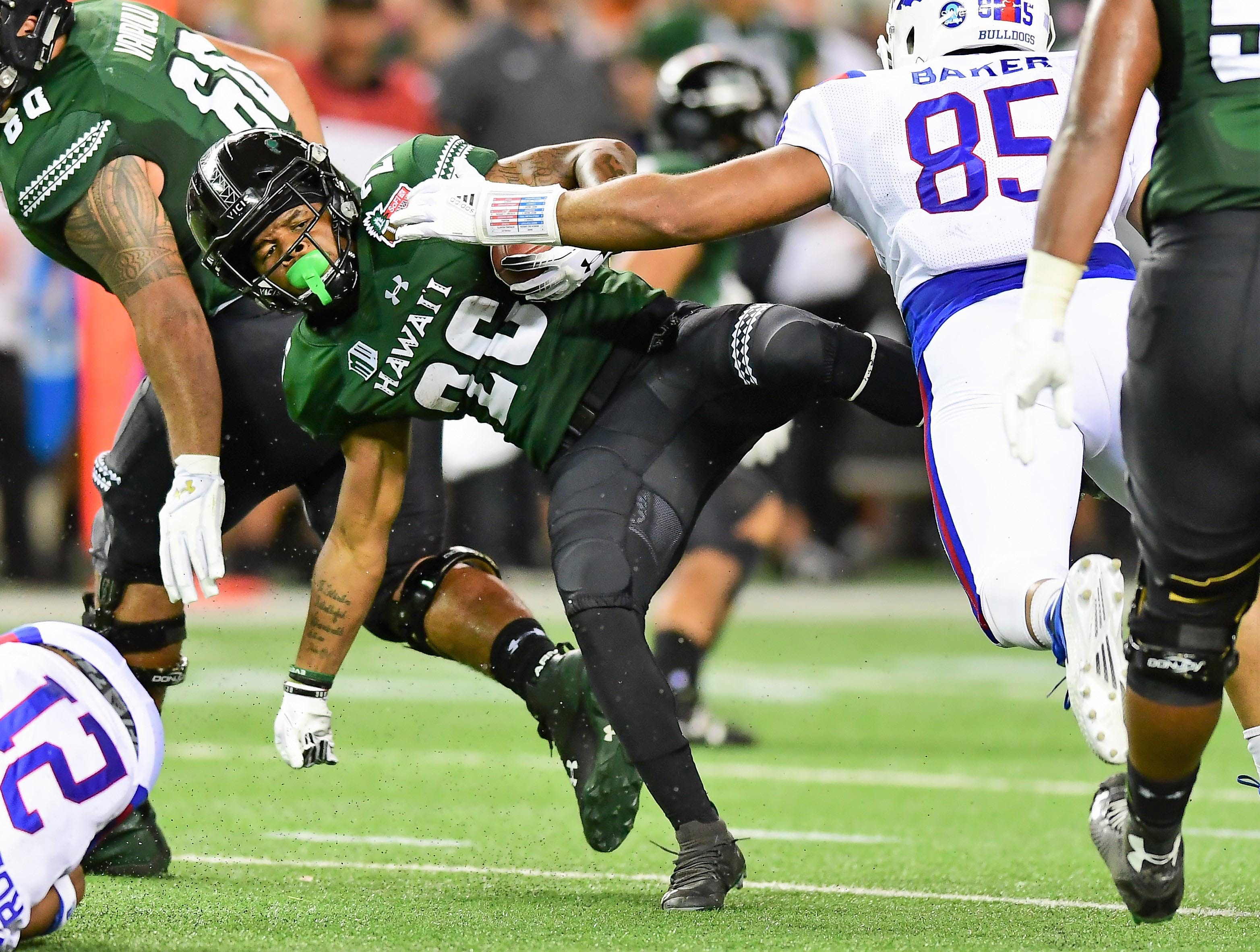 Hawaii Warriors running back Miles Reed (26) runs past Louisiana Tech Bulldogs defensive end Willie Baker (85) during the second quarter of the Hawaii Bowl.