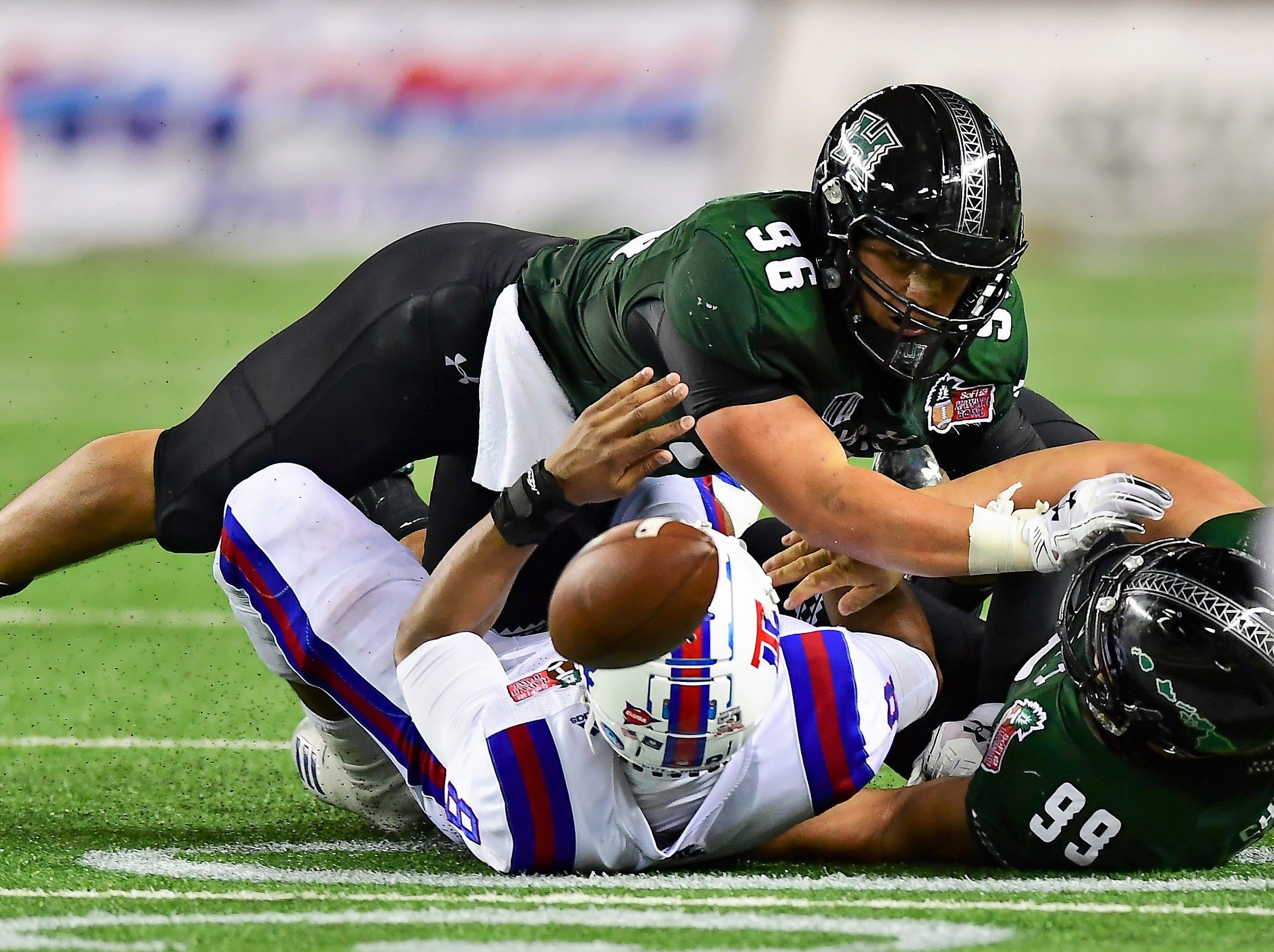Hawaii Warriors defensive linemen Zeno Choi (99) and Kaimana Padello (96) force a fumble from Louisiana Tech Bulldogs quarterback J'Mar Smith (8) during the second quarter of the Hawaii Bowl.