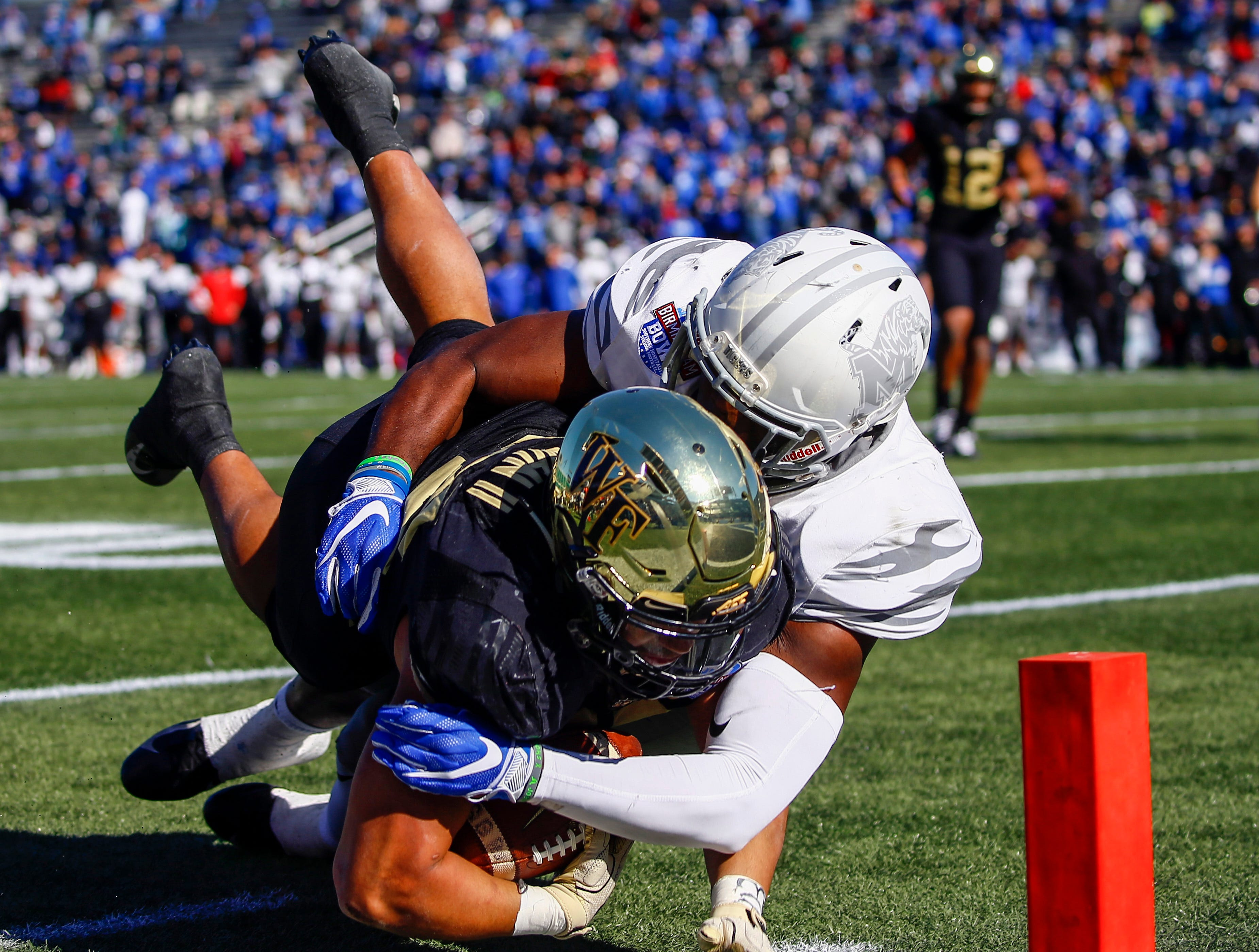 Wake Forest Demon Deacons running back Matt Colburn (22) is tackled just short of the goal line by Memphis Tigers linebacker Curtis Akins (7) during the first half of the Birmingham Bowl.