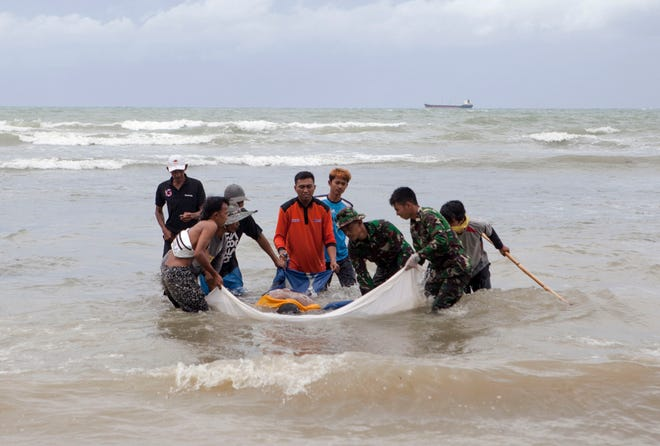 Indonesian officers carry a dead body after a tsunami on Anyer Beach in Karang Sugara village, Anyer, Banten, Indonesia, on Monday. According to the Indonesian National Board for Disaster Management, at least 281 people died and 1,016 others have been injured after a tsunami hit the coastal regions of the Sunda Strait on Saturday.