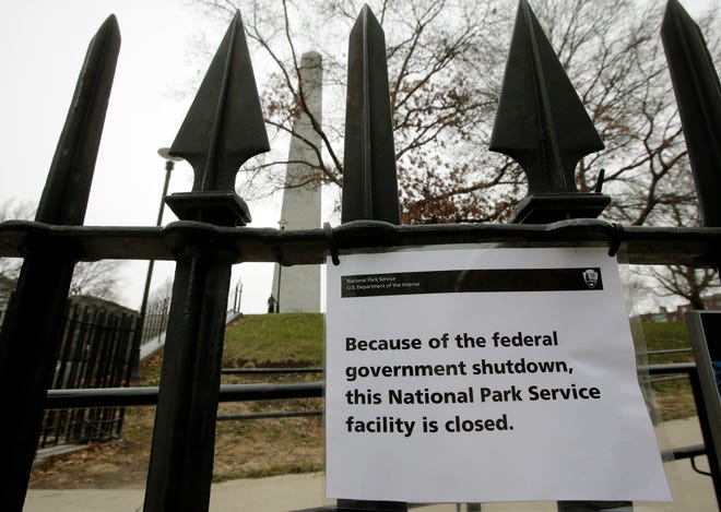 A sign is posted on a fence near an entrance to the Bunker Hill Monument, Monday, Dec. 24, 2018, in Boston. The historic site, erected to commemorate the Revolutionary War Battle of Bunker Hill, and run by the National Park Service, was closed Monday due to a partial federal government shutdown. The federal government is expected to remain partially closed past Christmas Day in a protracted standoff over President Donald Trump's demand for money to build a border wall with Mexico. (AP Photo/Steven Senne) ORG XMIT: MASR101