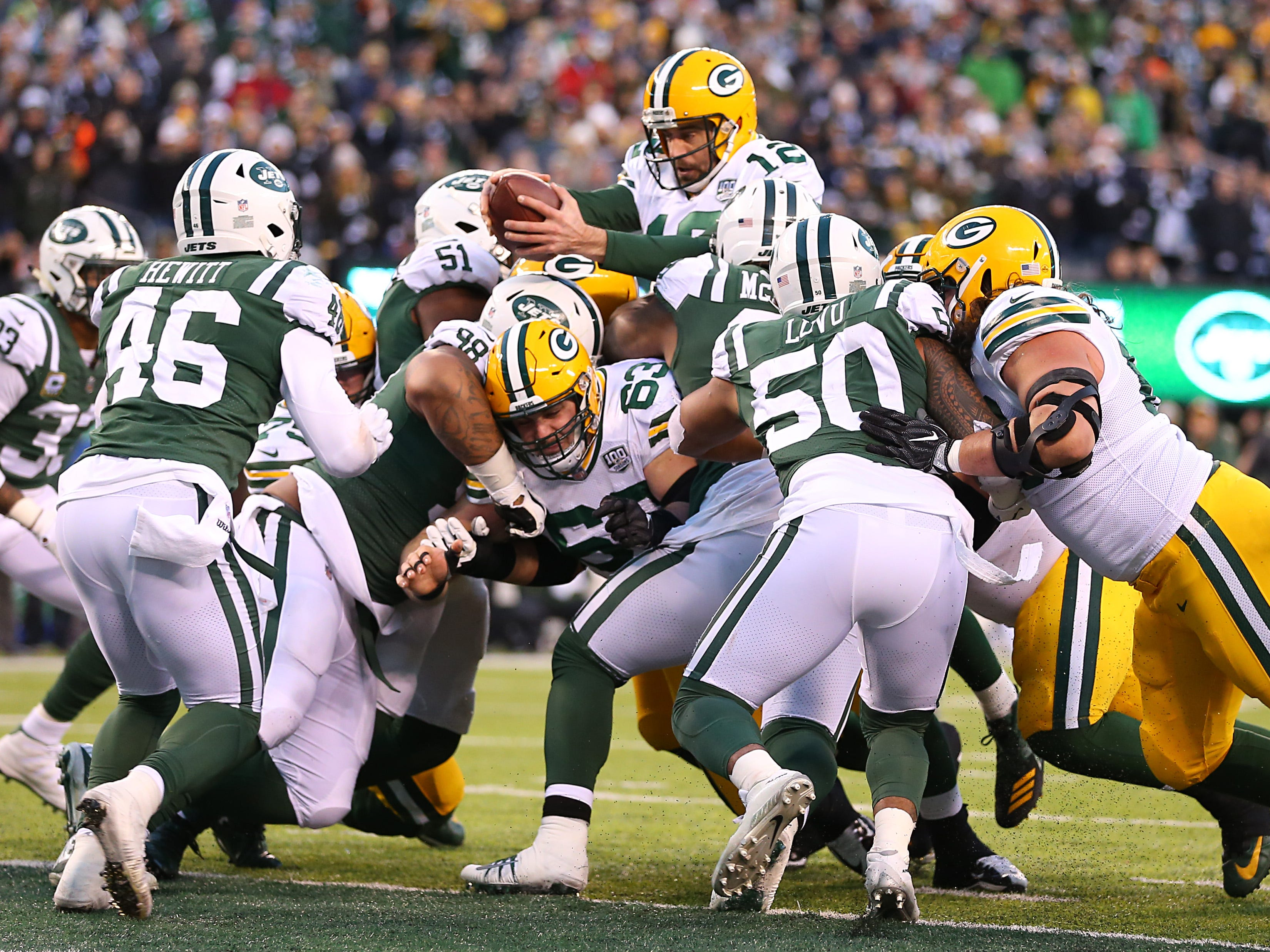 Week 16: Green Bay Packers quarterback Aaron Rodgers reaches over the line of scrimmage for a touchdown against the New York Jets at MetLife Stadium. The Packers won the game, 44-38, in overtime.