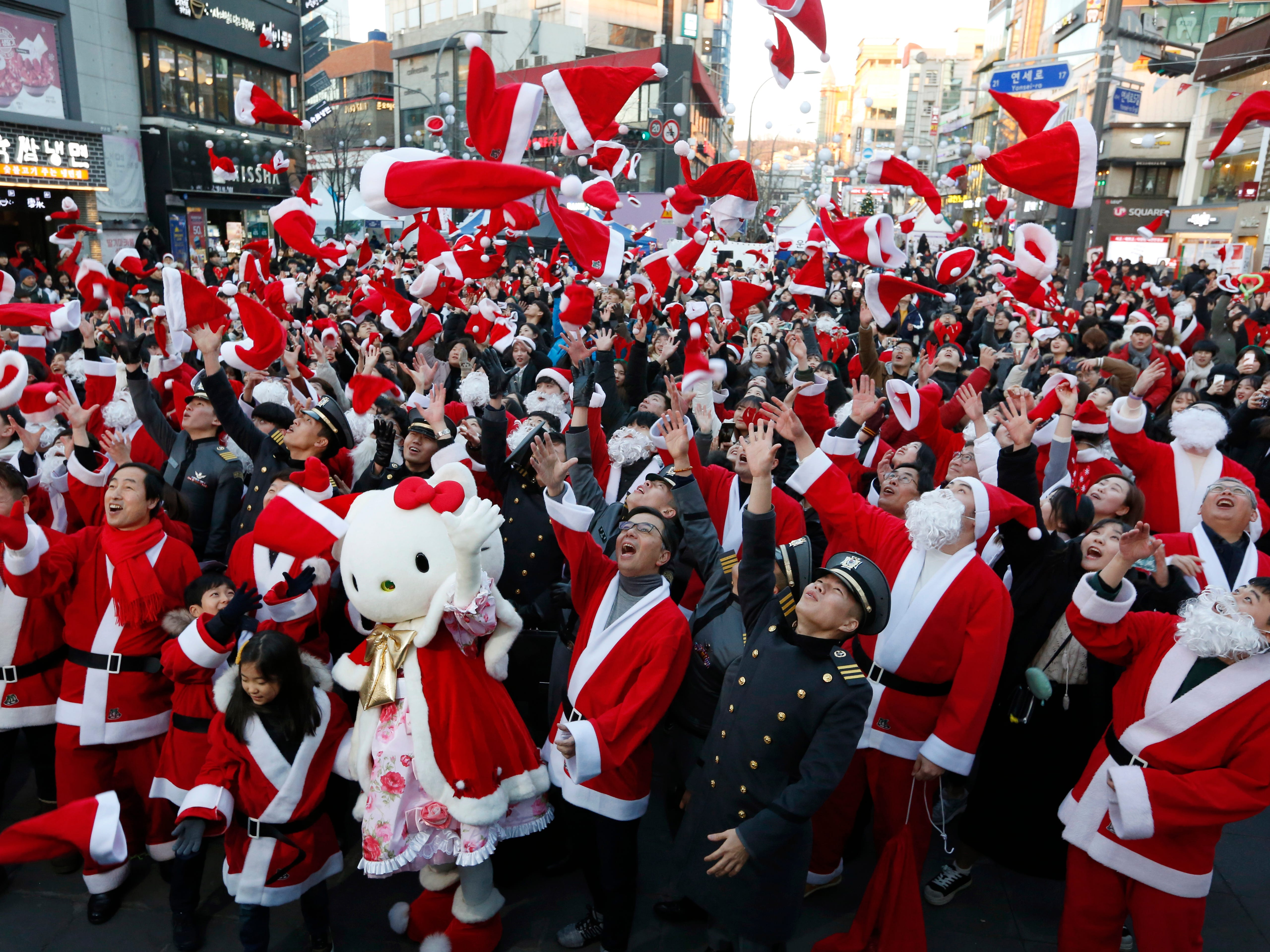 epaselect epa07247344 South Korean volunteers wearing Santa Claus costumes fling their hats into the air during a Christmas Eve charity event in Seoul, South Korea, 24 December 2018. The Seodaemun-gu local government office celebrated Christmas with a charity event, giving away gifts to 1,004 impoverished children.  EPA-EFE/JEON HEON-KYUN ORG XMIT: JHK01