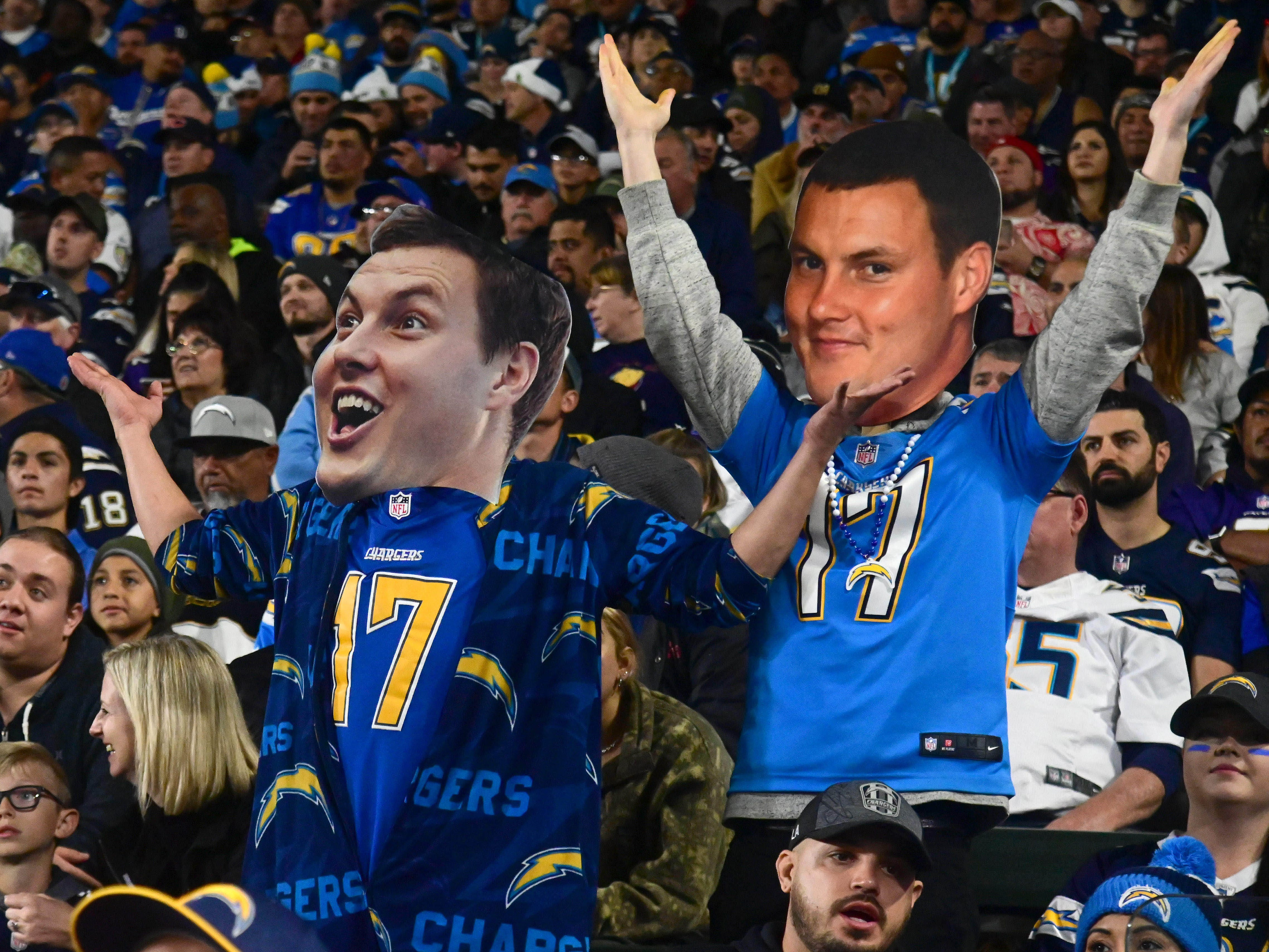Los Angeles Chargers fans pose with a cutout of the head of quarterback Philip Rivers during the game against the Baltimore Ravens at StubHub Center.