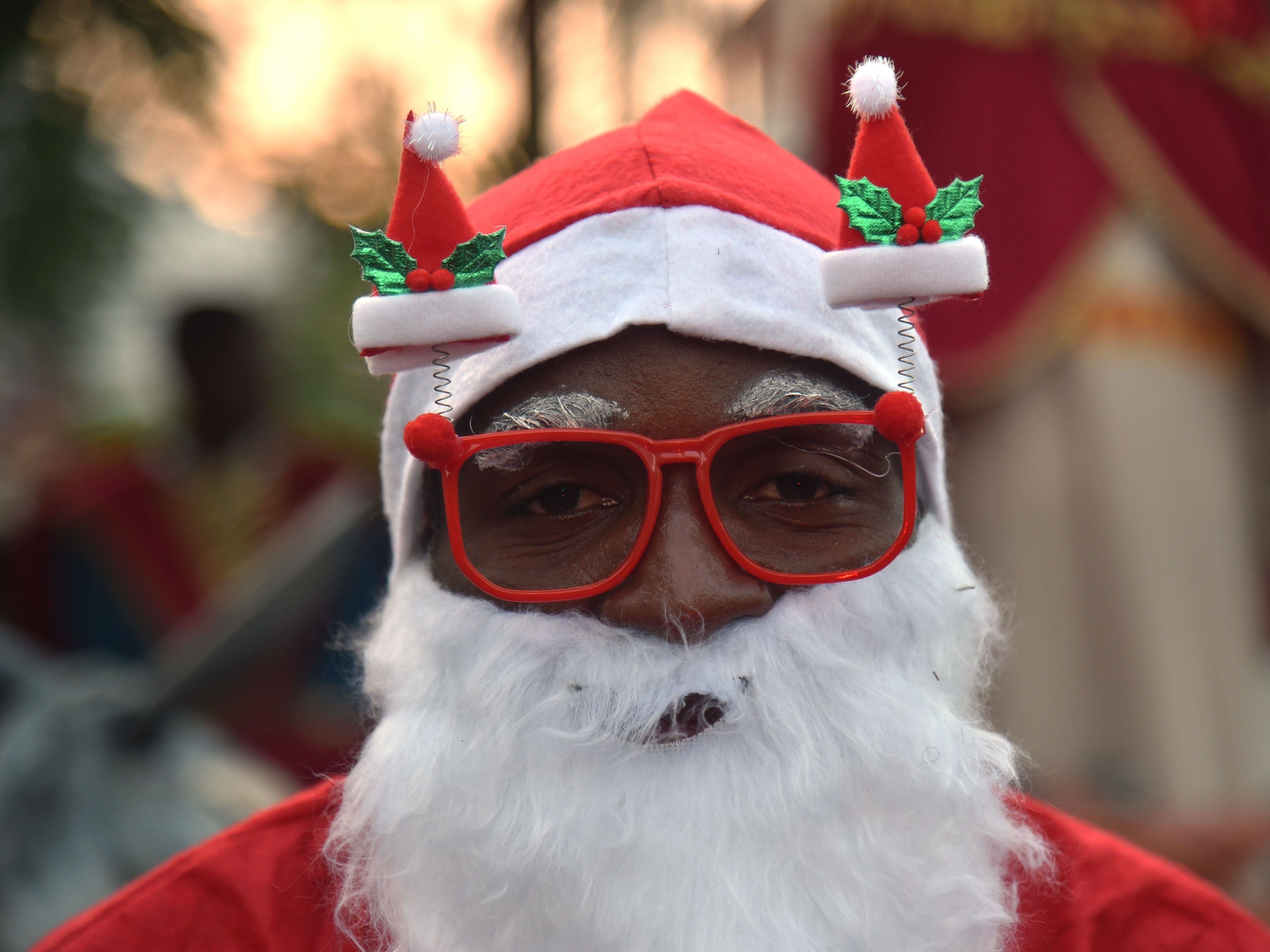 TOPSHOT - A Haitian man in a Santa Claus costume participates in a Christmas Parade (Parad Nwel in Haitian creole) on the streets of the commune of Petion Ville, in the Haitian capital Port-au-Prince, on December 23, 2018. (Photo by HECTOR RETAMAL / AFP)HECTOR RETAMAL/AFP/Getty Images ORG XMIT: 2246 ORIG FILE ID: AFP_1BT26Y