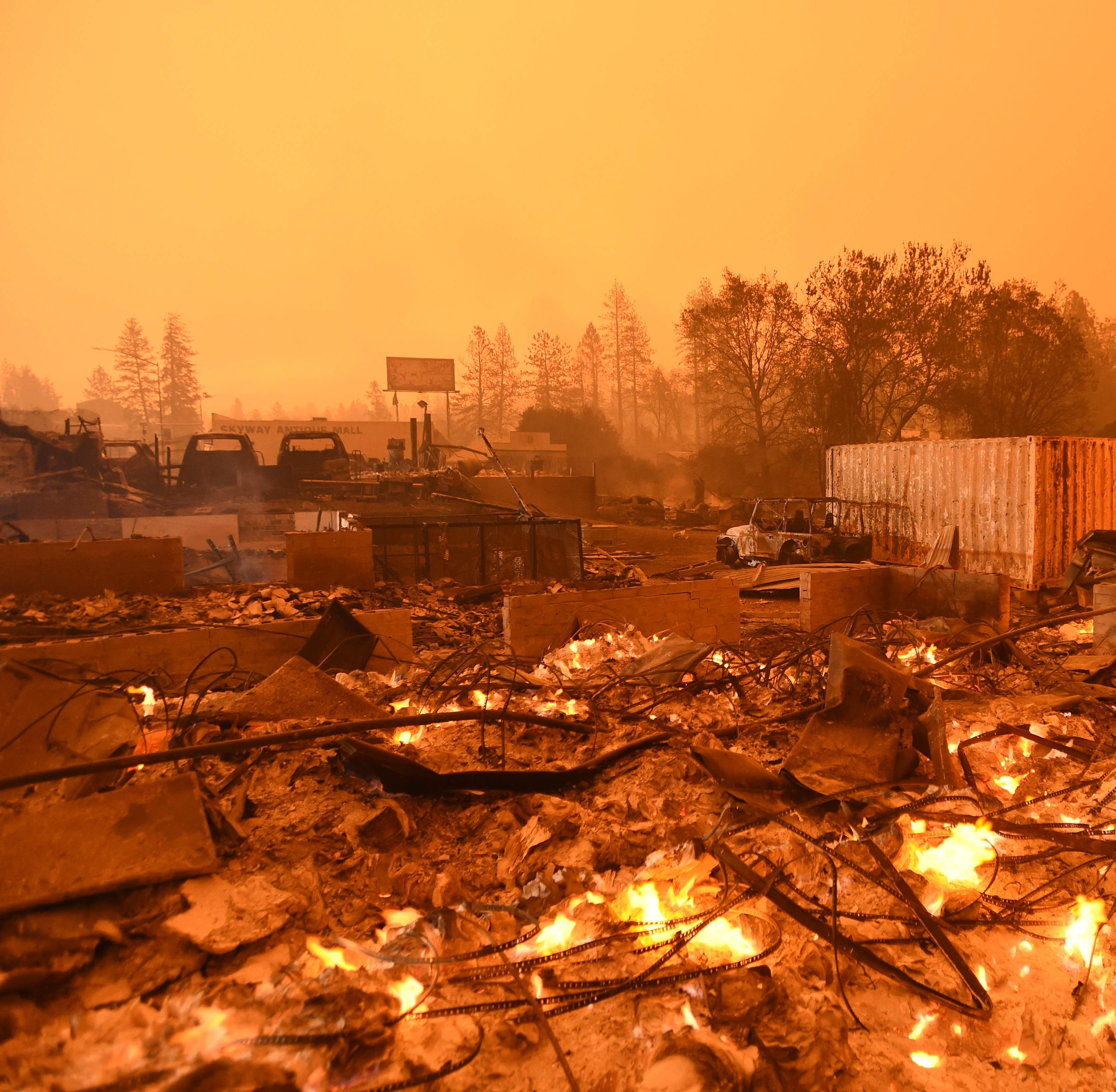 Businesses burn under a darkened smokey sky in Paradise on Nov. 9.
