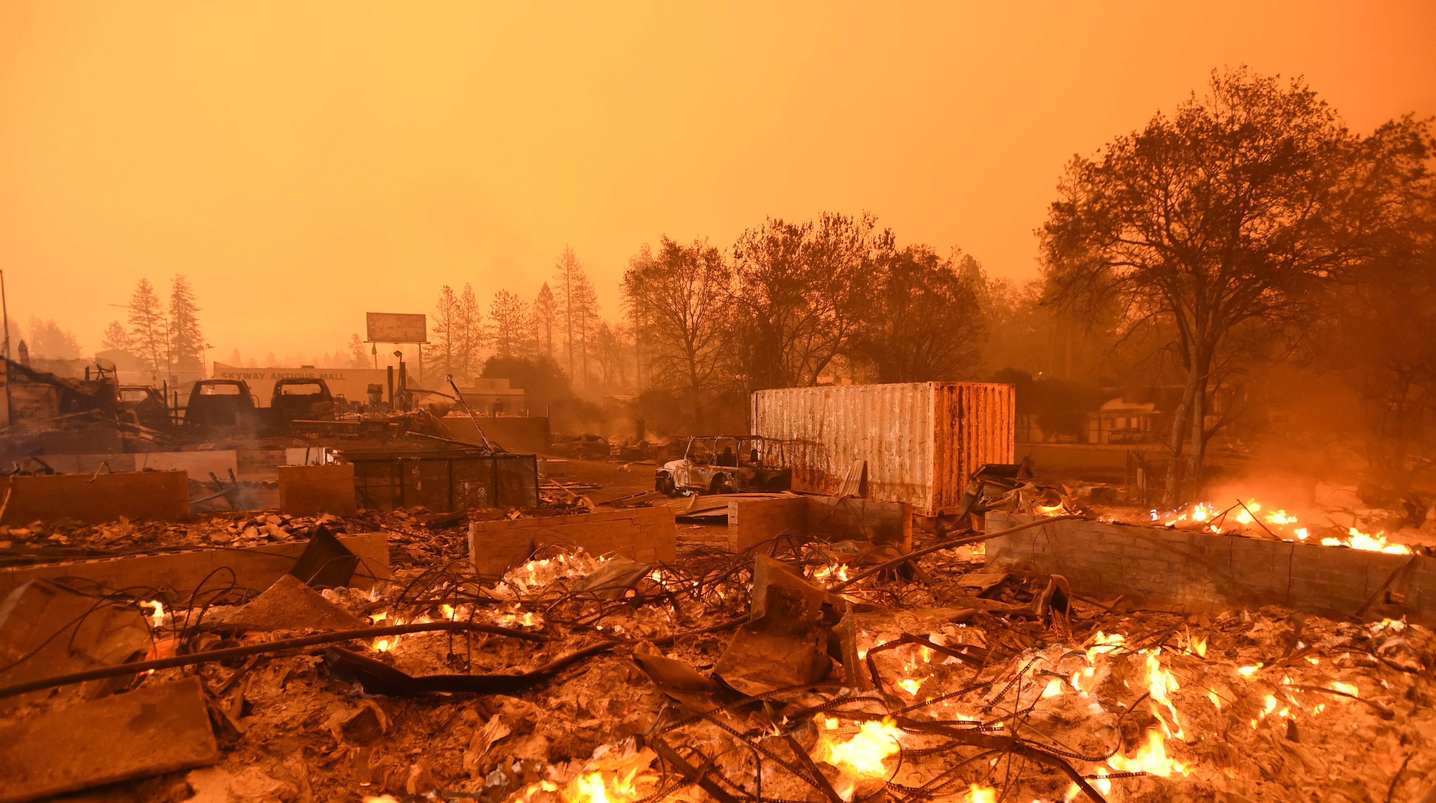 Businesses burn under a darkened smokey sky in Paradise on Nov. 9.