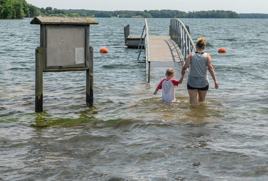 Peggy Whitworth and her grandson Samuel Brown wade through high water to a dock at Green Pond Landing on Lake Hartwell in June. The lake is above full pool, which many business owners on the lake think is good.