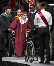 Westside High School graduate Logan Wires gets out of a wheelchair to walk to get his diploma from Principal Kory Roberts during graduation in Littlejohn Coliseum in Clemson on Saturday, May 26.