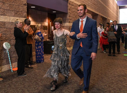 Joy Martin of Gaston, S.C. is escorted by Hunter Renfrow, a Clemson football wide receiver, during the Come Dream With Me prom in the Civic Center of Anderson on Sunday night. A crowd with 600 special needs children and adults of all ages and family took part in a Candy Land theme prom with dancing, getting escorted down a colorful hallway, plus music by Landon Wall. Four Clemson football players, Hunter Renfrow, Cole Renfrow, Clay Cooper, and Elijah Turner, joined in with many community volunteers to help.