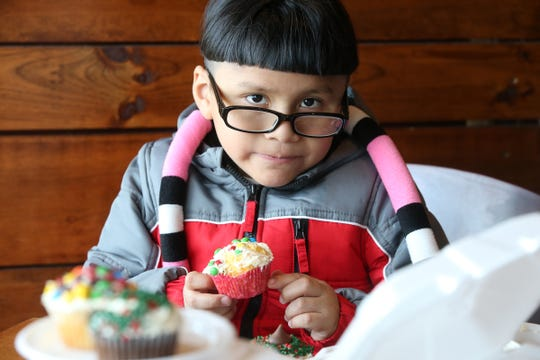 Marmin Pena, 6, of Asbury Park enjoys a cupcake during the annual Christmas Community Dinner at Langosta Lounge in Asbury Park, NJ Tuesday, December 25, 2018.