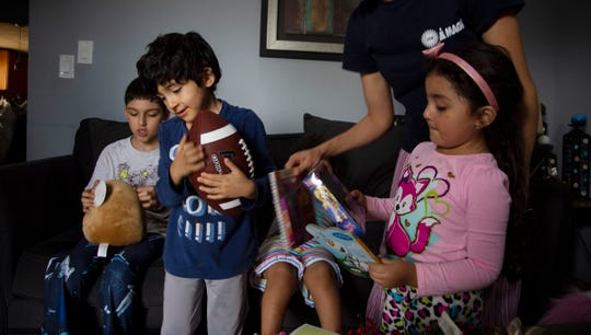 Ubaldo Reyna, 8, left, of Detroit, checks out his new Plushie as his brother Dylan Reyna, 5, hugs a new football and sister Alexia Reyna looks at a selection of books after they recieved a bag of toys from Jimmy's Kids. Jimmy's Kids supplied over 300 metro Detroit families with toys handed out by mitzvah day interdenominational volunteers in Detroit Tuesday, Dec. 25, 2018.