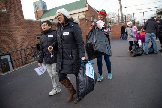 Adam Tlaib, left, joins his mom newly elected congresswoman Rashida Tlaib and cousin Hayat Jaber to deliver toys they picked up in the parking lot of St. Stephen Lutheran Church in Detroit as part of Jimmy's Kids on Detroit Tuesday, Dec. 25, 2018.