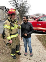 Barn Chandler, firefighter with the Washington Township Fire Department, with Anand Nittur, 27. Nittur was a resident of the Sterling Troy Apartments that caught fire on Christmas morning. Later in the afternoon, Chandler retrieved NitturÕs medication from his apartment in the evacuated building.