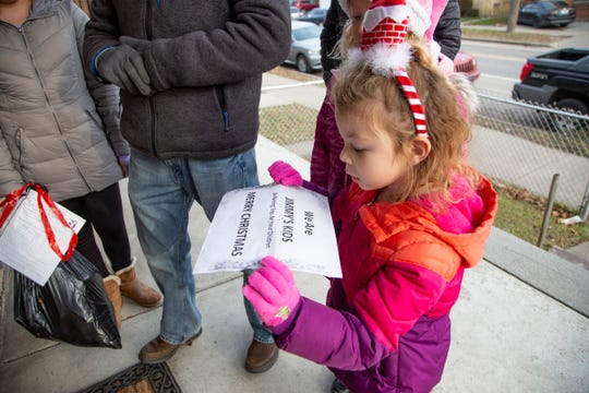 Jimmy's Kids volunteer Mila Rose, 5, makes sure she is holding up her sign correctly as she and her family deliver toys to a family in Detroit on Tuesday, Dec. 25, 2018.