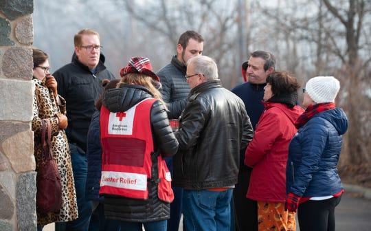 Red Cross workers assist displaced residents at the scene of a huge fire on Christmas morning at the Sterling Troy Apartments in in Sterling Heights.