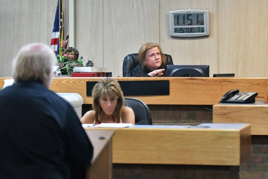 Magistrate Linda Mack sits behind court clerk Marianne Szlinis during a video arraignment with attorney Marshall Goldberg, left, at 34th District Court in Romulus, Mich. on Dec. 25, 2018. 34th District court handles the arraignments for Wayne County and Detroit that must take place on Christmas.