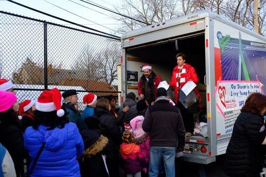 Hundreds of volunteers empty a donation truck to distribute to southwest Detroit families on Christmas.