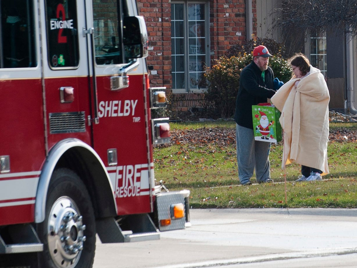 Possible displaced residents from a large apartment fire at the Sterling Troy Apartments stand outside the fire scene area on Christmas Day in Sterling Heights.