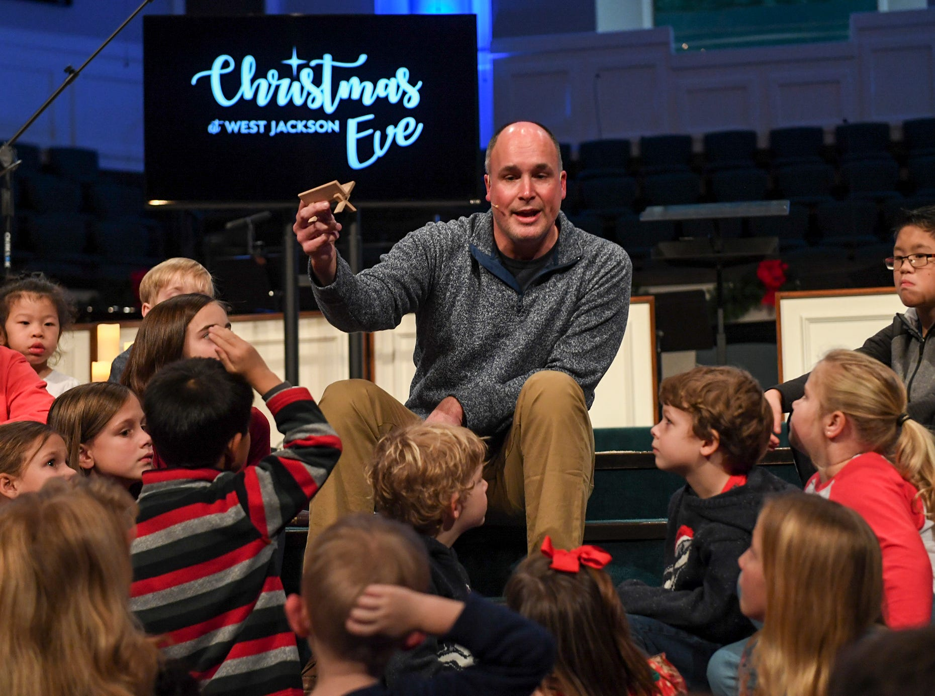 West Jackson Baptist Church Pastor Andy Neely talks to children about the gift of Jesus Christ during Christmas Eve at West Jackson, Monday, Dec. 24.