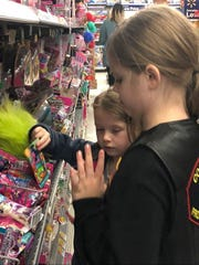 Lillyana Ferguson grabs a Trolls toy as Blakelyn Edwards looks on as they shop at Walmart-North. Combat Veterans Motorcycle Association raised $2500 for veterans' kids, who were each allotted $200.