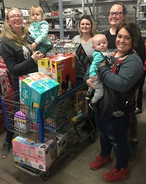 "Kristina Collins, Aundie ""Hootie"" Pounds, Carol ""Christmas"" Kail, Rachael ""Schatzi"" Wilkes at Walmart-North picking out essentials for Collins' youngest child. Combat Veterans Motorcycle Association raised $2500 for veterans' kids, who were each allotted $200."