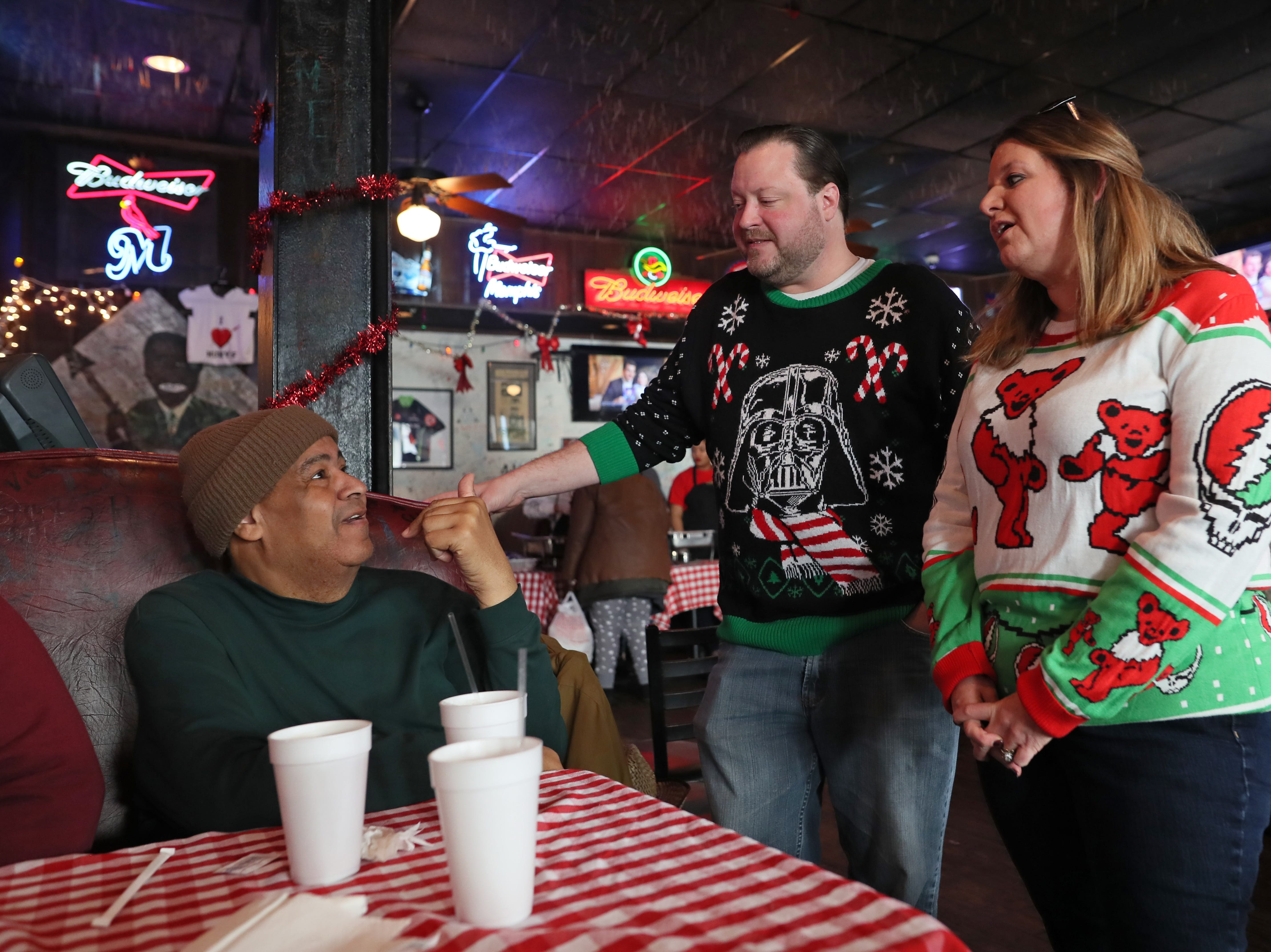 Michelle Hurt and her husband Will chat with Herb (last name withheld) as they serve free meals and hand out warm clothing at the Huey's Downtown restaurant on Christmas Day Tuesday, Dec. 25, 2018.