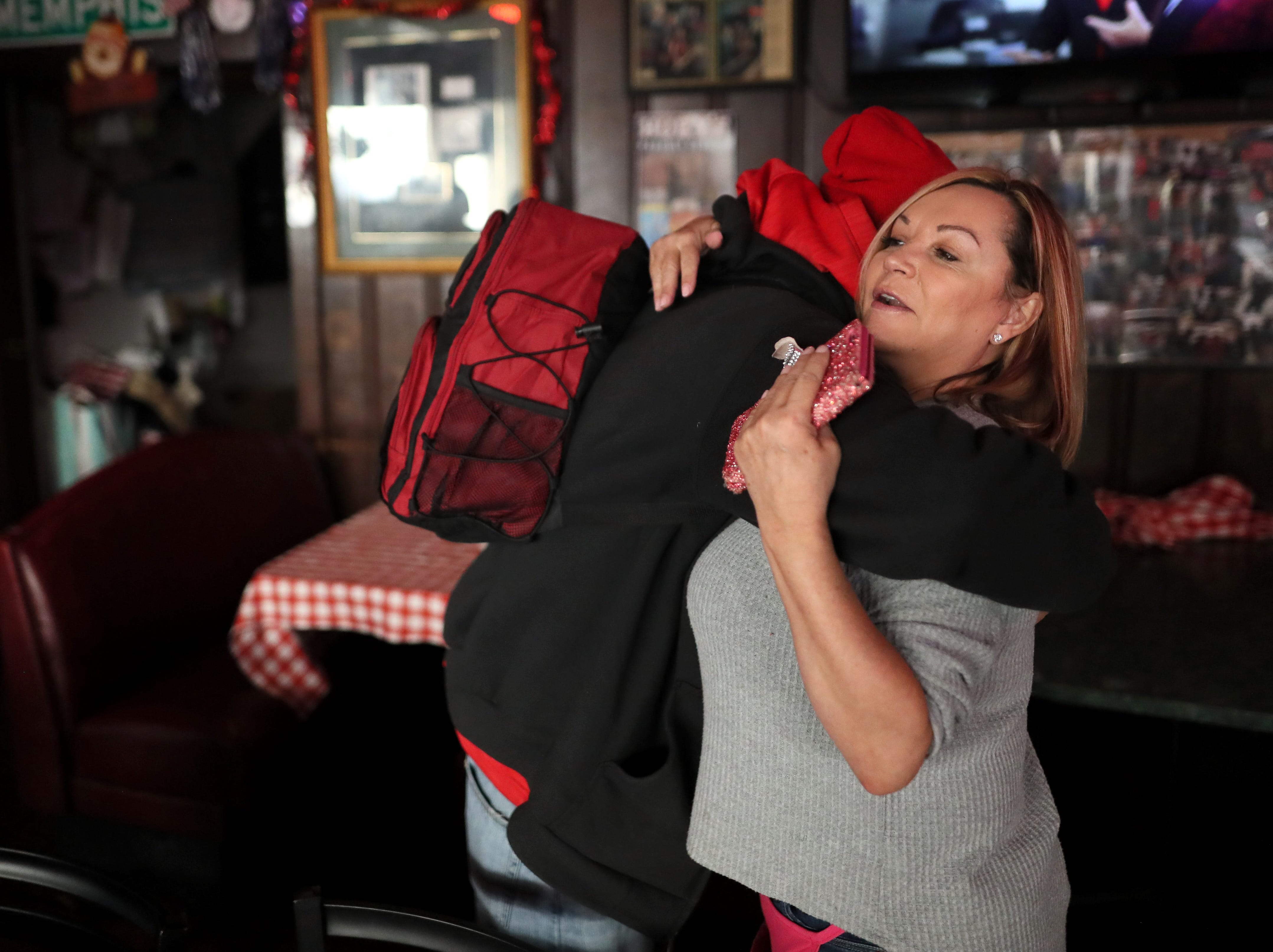 Christopher Freen hugs volunteer Sarah Nickell as she helps to serve free meals and hand out warm clothing at the Huey's downtown restaurant on Christmas Day Tuesday, Dec. 25, 2018.