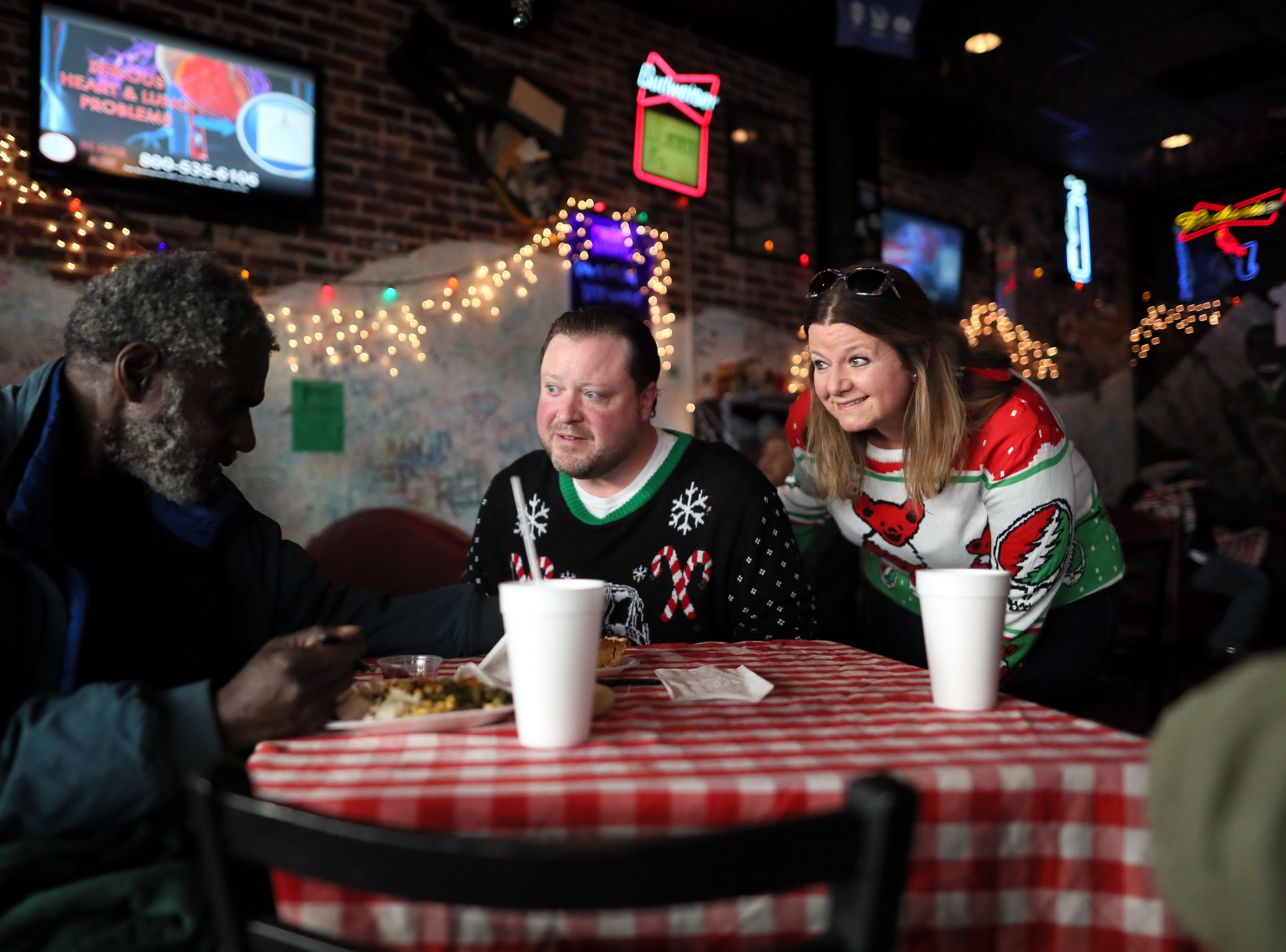 Michelle Hurt and her husband Will chat with guests as they serve free meals and hand out warm clothing at the Huey's downtown restaurant on Christmas Day Tuesday, Dec. 25, 2018.
