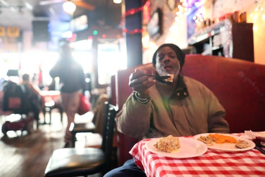 J.R. Fletcher Ferguson holds up a forkfull of his Christmas meal as Huey's Downtown restaurant opens its doors to serve a holiday lunch and hand out warm clothes on Tuesday, Dec. 25, 2018.