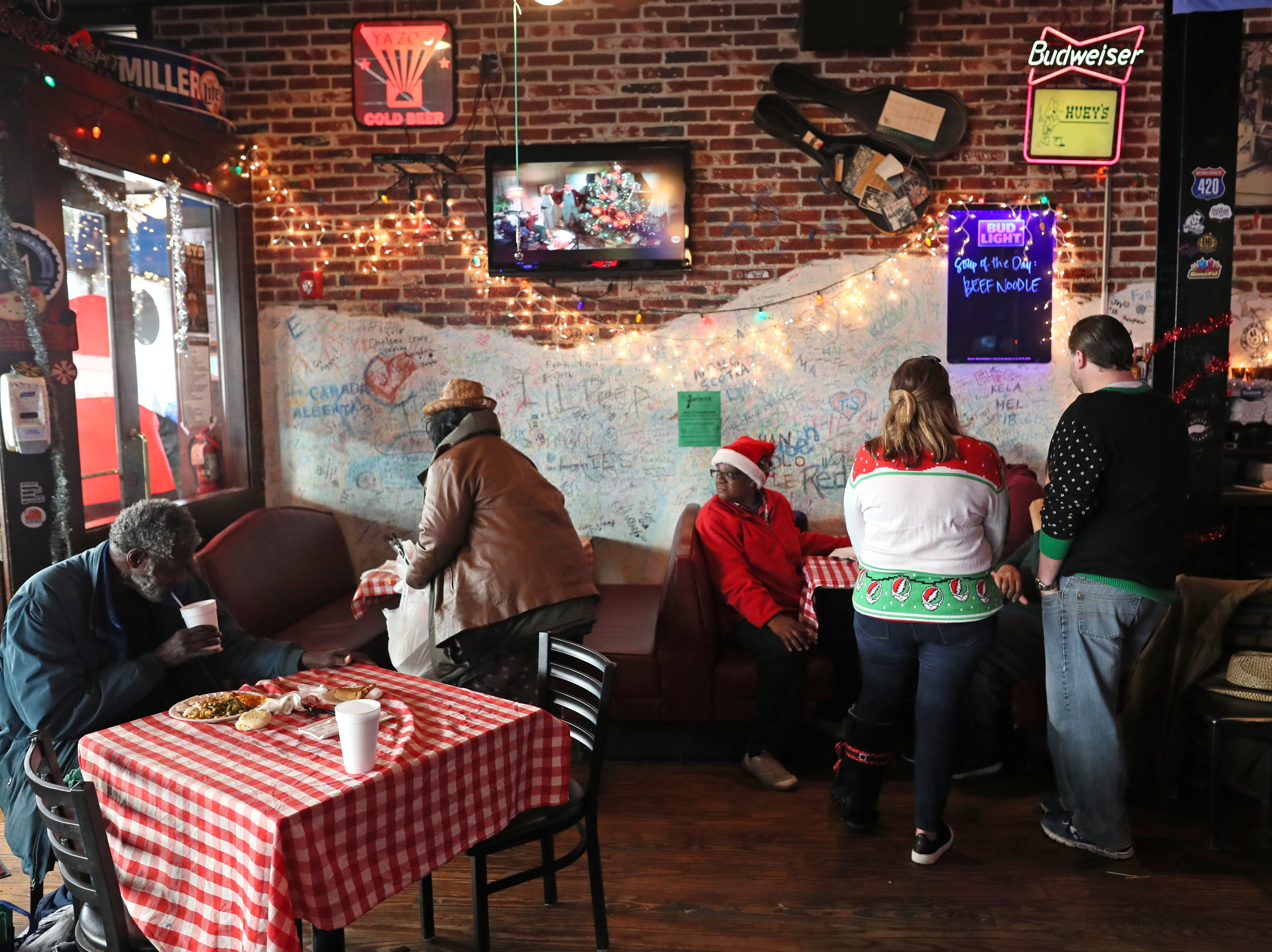Volunteers serve turkey with all the trimmings and hand out warm clothing at the Huey's downtown restaurant on Christmas Day Tuesday, Dec. 25, 2018.
