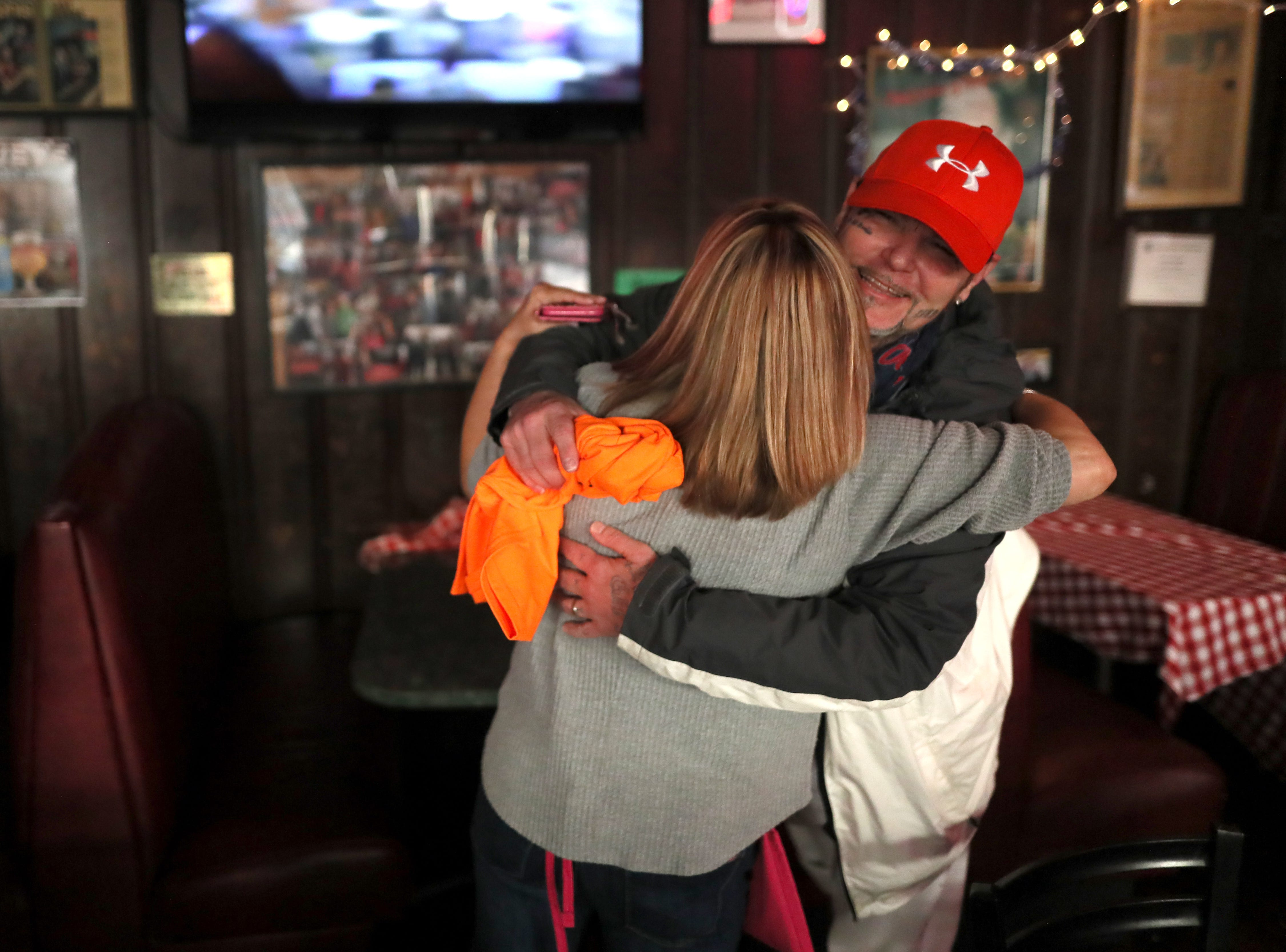 Joseph Marchisio hugs volunteer Sarah Nickell as she helps to serve free meals and hand out warm clothing at the Huey's Downtown restaurant on Christmas Day Tuesday, Dec. 25, 2018.