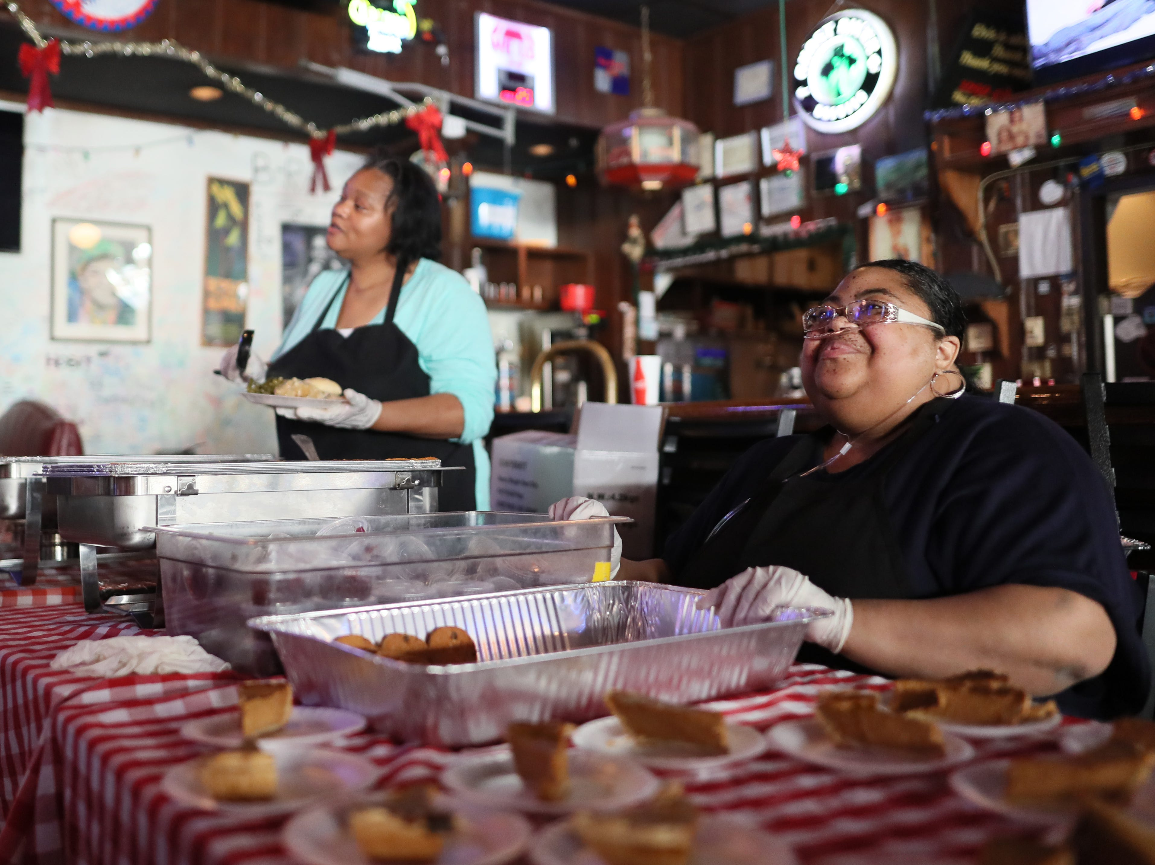 Patrice Thompson, left, and her cousin Shericka Cotton serve free meals and hand out warm clothing at the Huey's Downtown restaurant on Christmas Day Tuesday, Dec. 25, 2018.