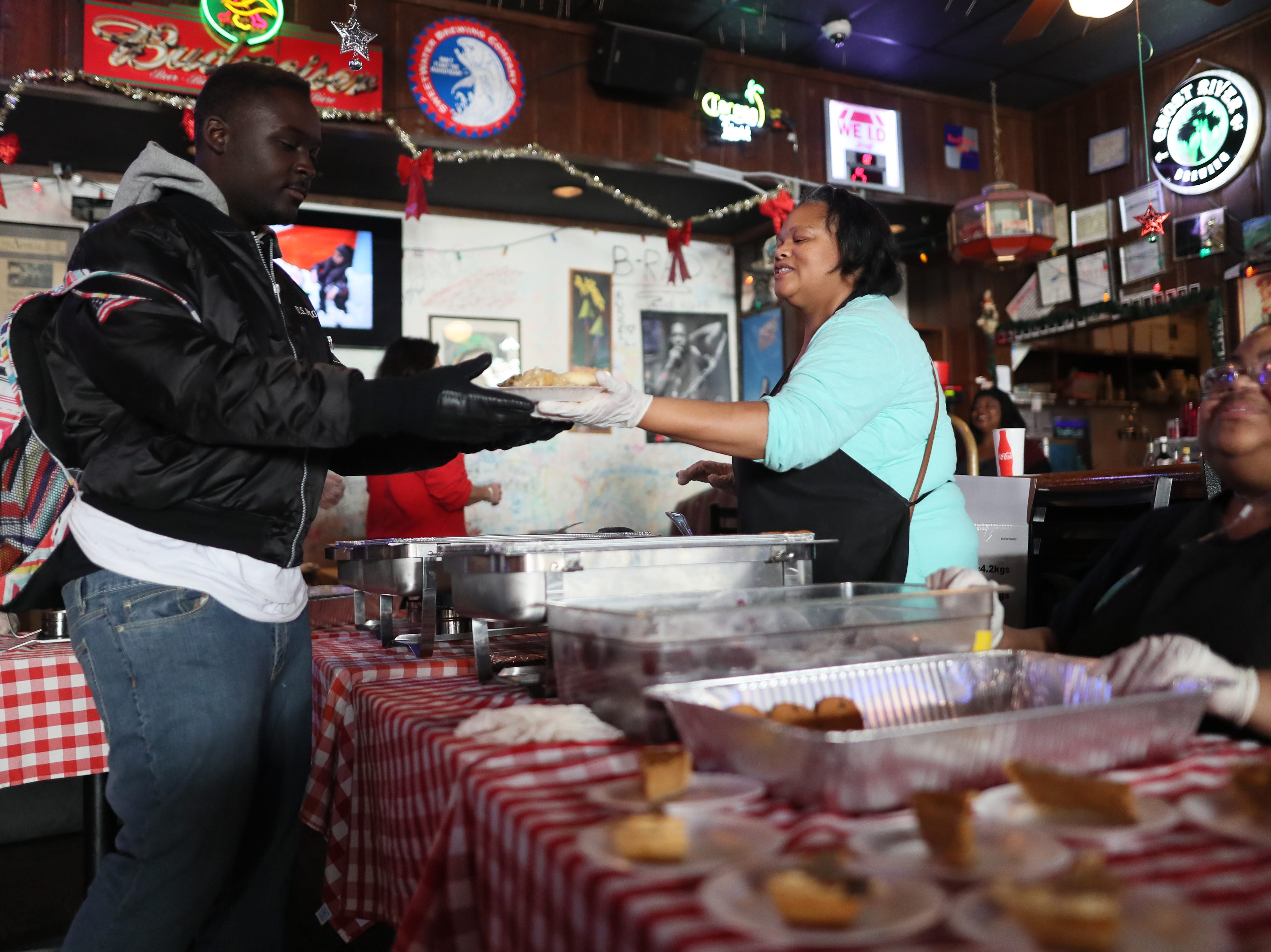 Patrice Thompson, center, and her cousin Shericka Cotton serve free meals and hand out warm clothing at the Huey's downtown restaurant on Christmas Day Tuesday, Dec. 25, 2018.