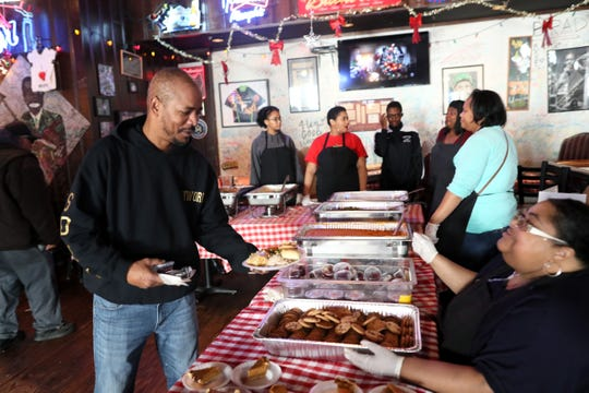 Volney Ewing, left, and Shericka Cotton volunteer to serve free meals and hand out warm clothing at the Huey's Downtown restaurant on Christmas Day Tuesday, Dec. 25, 2018.
