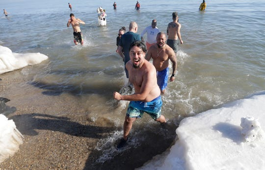 Rolando Gonzalez and his father, Rolando Gonzalez (behind), escape from the icy waters of Lake Michigan during the 2018 Polar Bear Plunge at Bradford Beach. The tradition continues in 2019 with Tuesday's plunge.