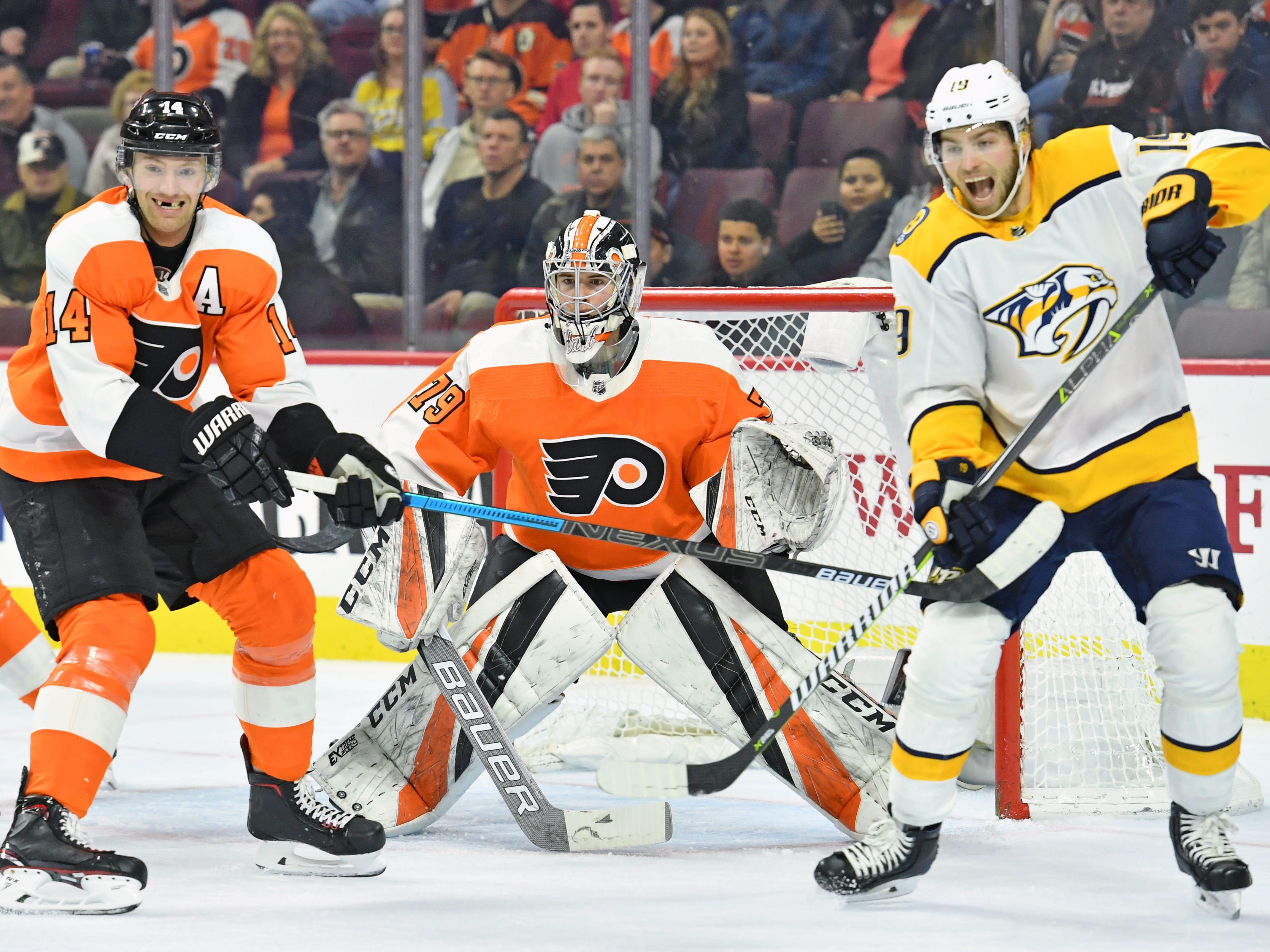 Philadelphia Flyers center Sean Couturier (14) battles with Nashville Predators center Calle Jarnkrok (19) in front of goaltender Carter Hart (79) during the first period at Wells Fargo Center.