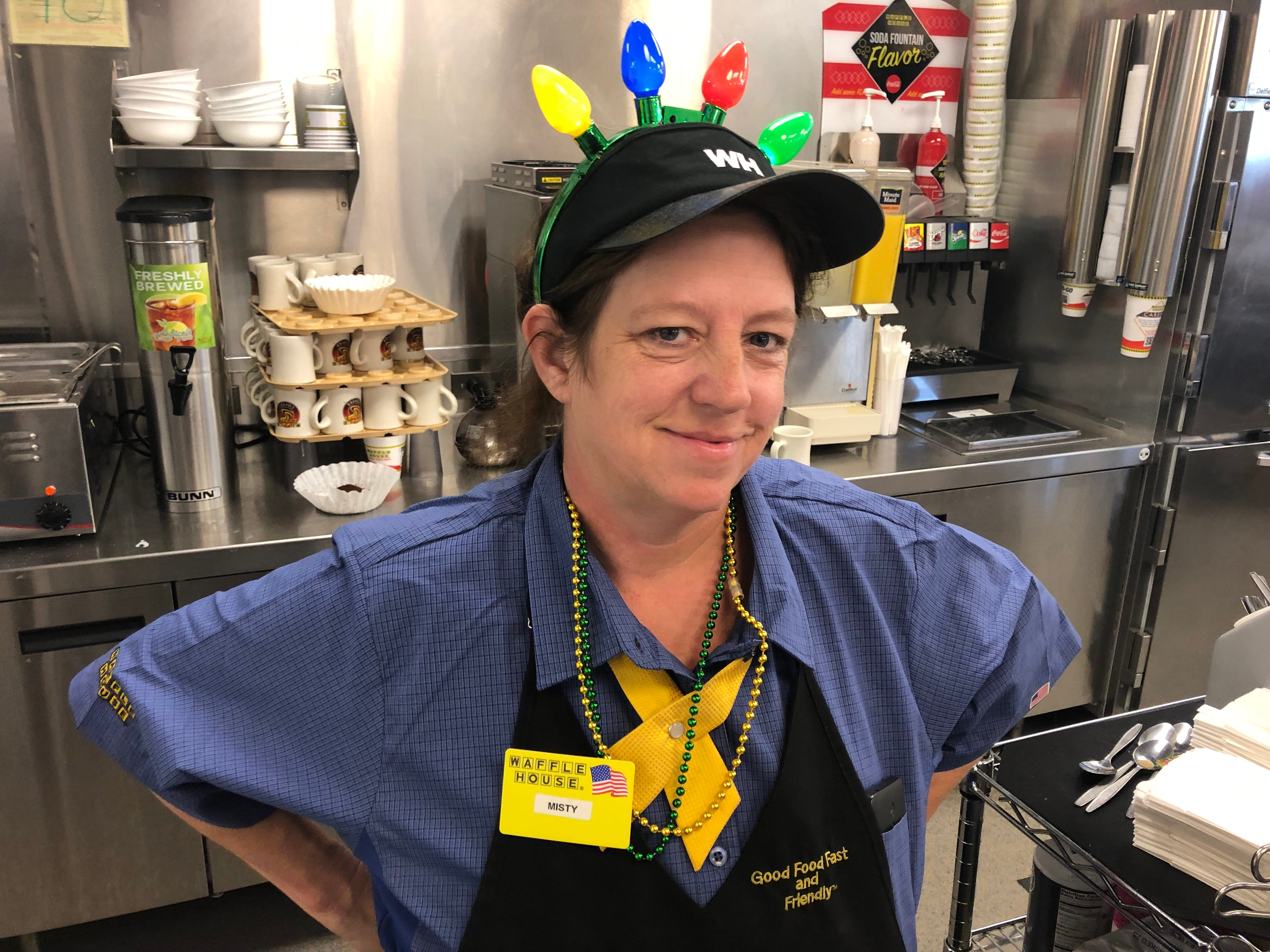 "A Waffle House server shows off her new Christmas light bulbs headgear Christmas morning that she got from ""Santa"" George Armistead, a former Metro Councilman"