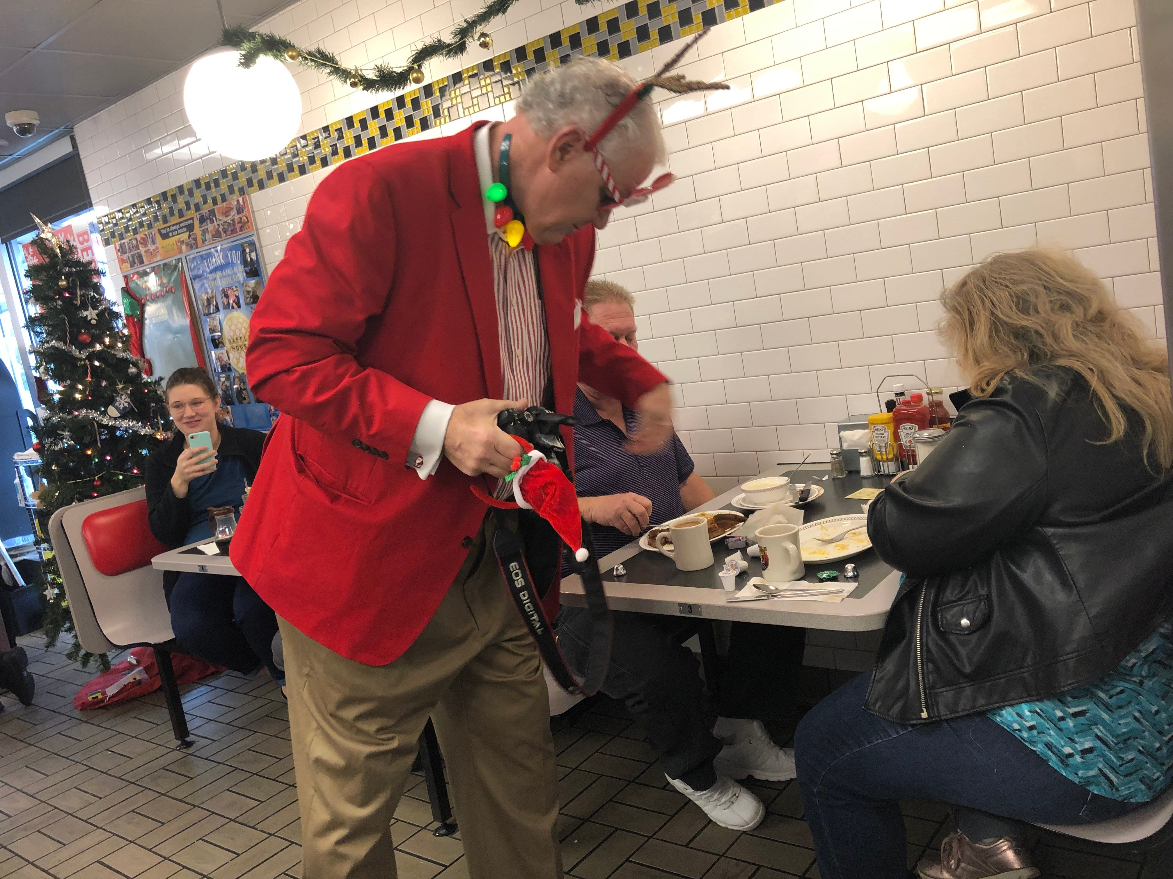 """Santa"" George Armistead puts candy on the table of some customers on Christmas morning 2018 at the White Bridge Road location of Waffle House"