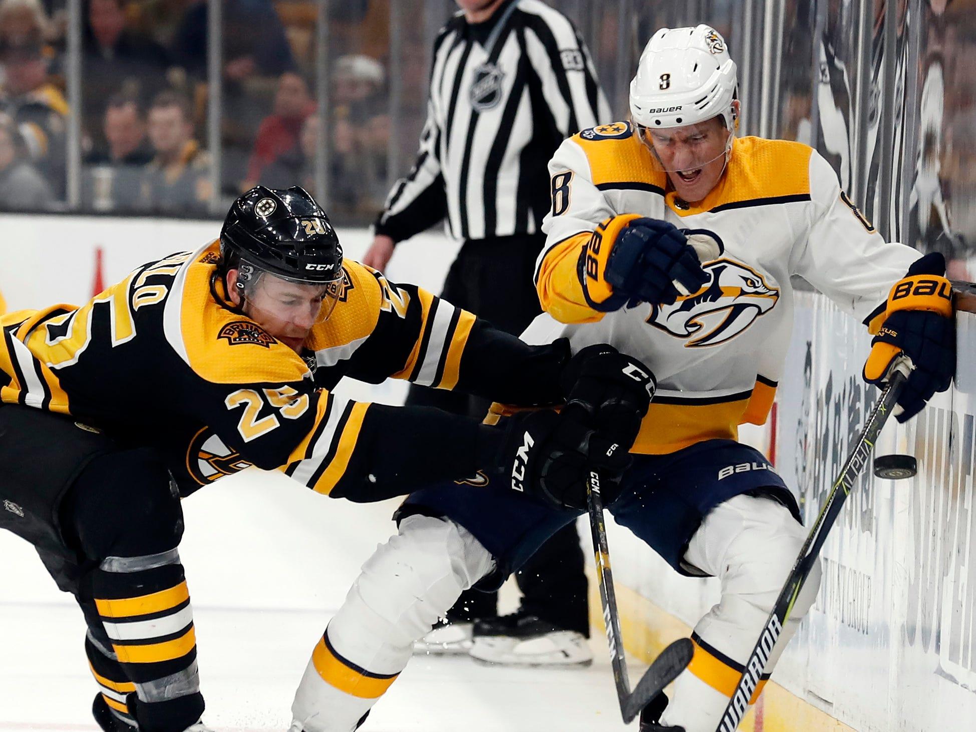 Boston Bruins defenseman Brandon Carlo (25) checks Nashville Predators center Kyle Turris (8) into the boards during the third period of Boston's 5-2 win at TD Garden.