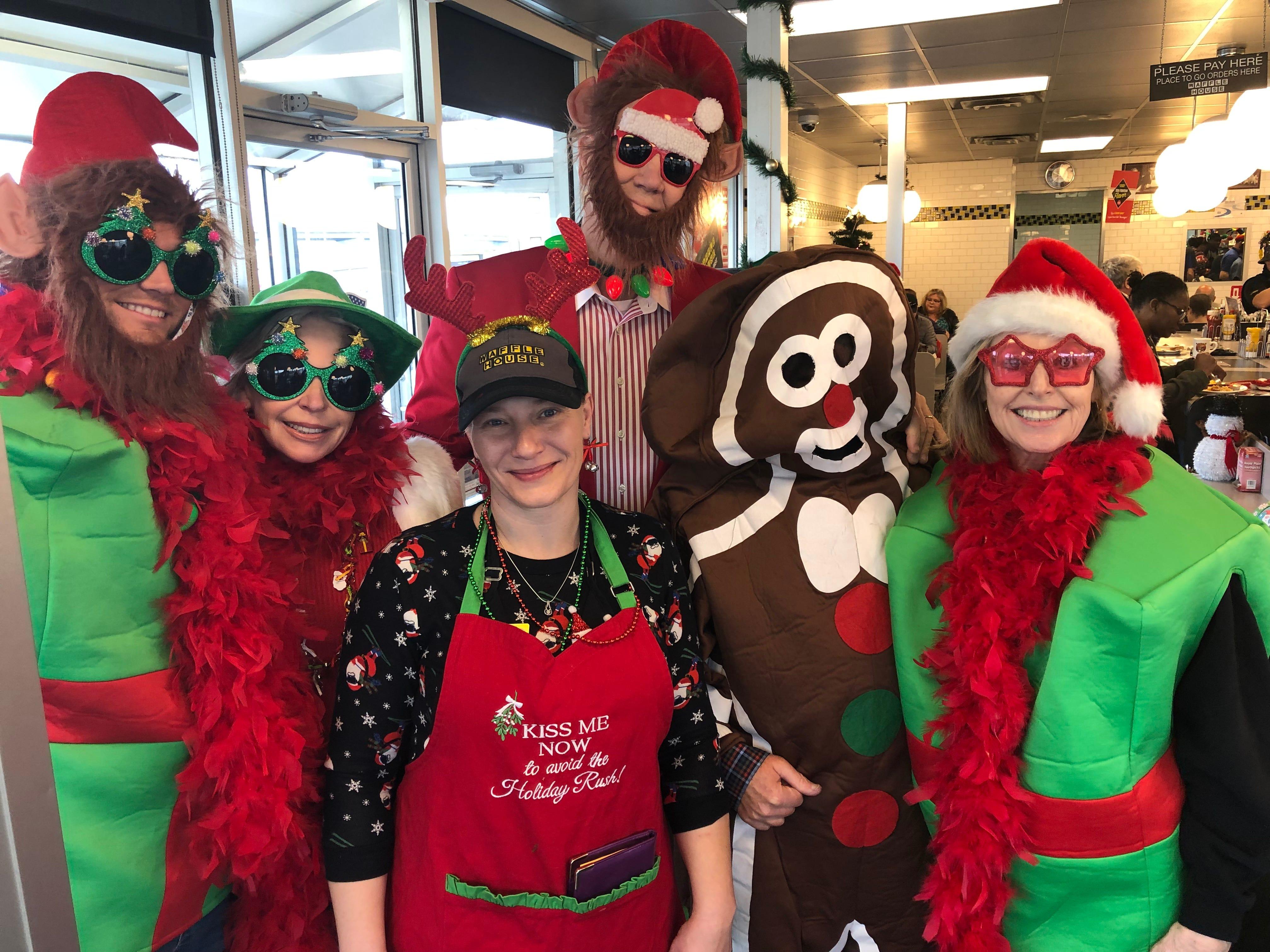 """Santa"" George Armistead, center back, and his wife, Lydia, and neighbors pose for a pic after leading a West Nashville Waffle House in Christmas carols Chrismas morning 2018"