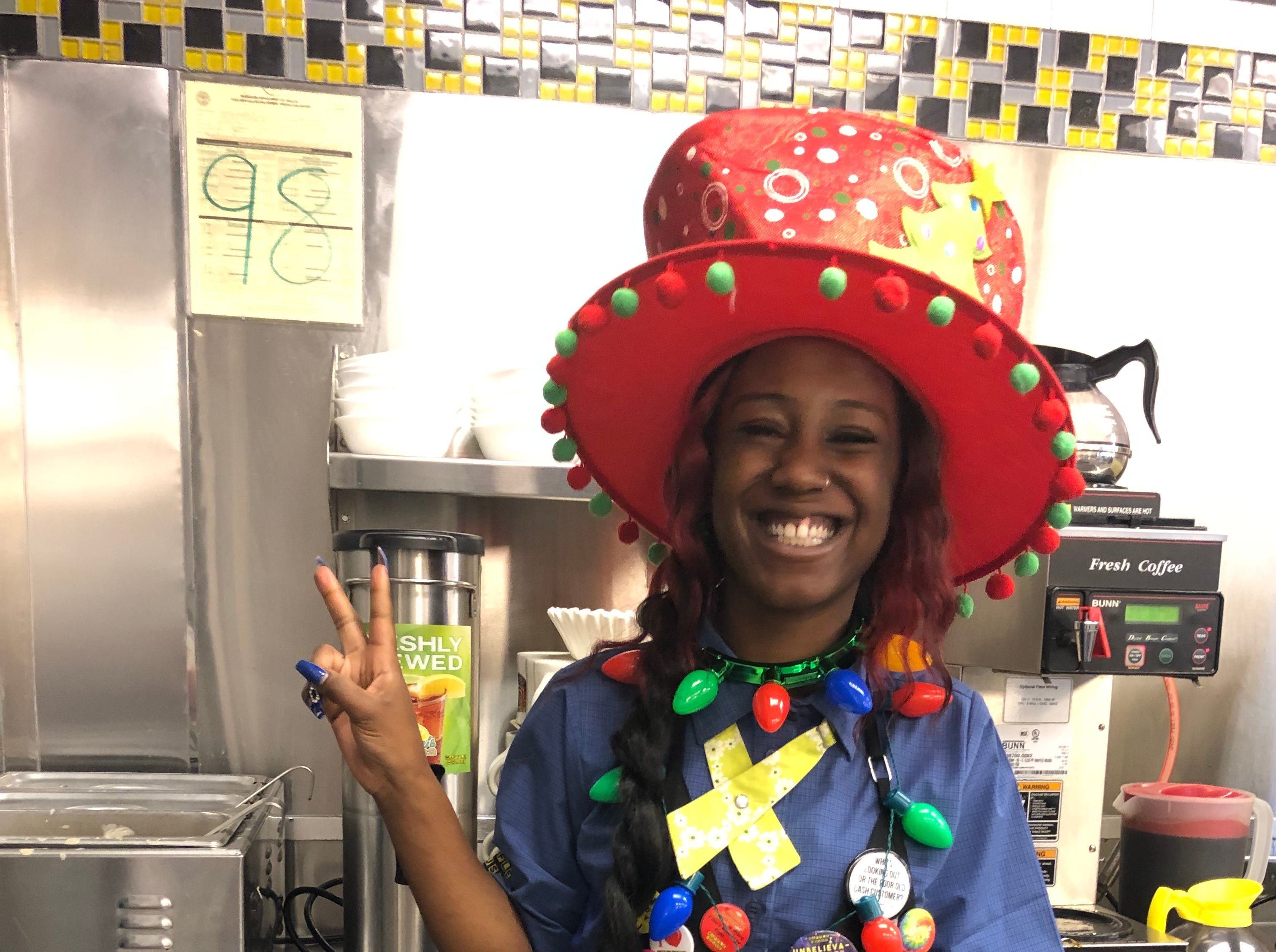 "A Waffle House hostess at the location on White Bridge Road enjoys the Christmas hat brought to her by ""Santa"" George Armistead on Christmas morning 2018"