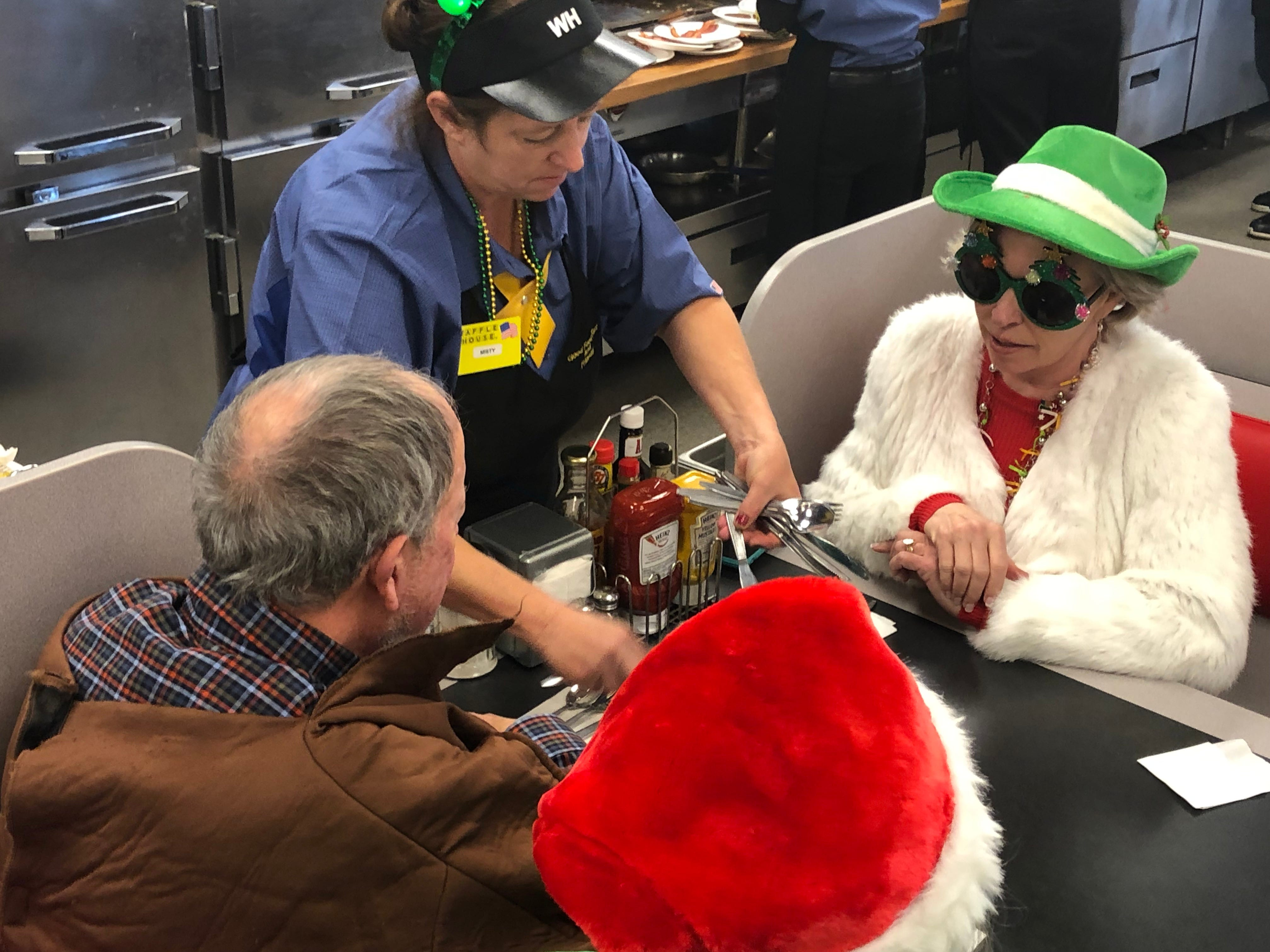 Lydia Armistead, right, in the green hat, relaxes with some of her neighbors at the White Bridge Road Waffle House Christmas morning 2018 after they passed out candies and cash.