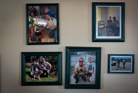 In the bottom row center photo, Kyle Plussa, a Florida Fish and Wildlife Conservation Commission officer, holds a gopher tortoise he rescued. The photo hangs in the hallway at FWC division of law enforcement on Dec. 20, 2018. Plussa is recovering from a life-altering car crash in August.