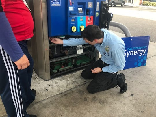 Officials from the Collier County Sheriff's Office, code enforcement and the Florida Department of Agriculture examine fuel pumps for evidence of credit card skimmers.