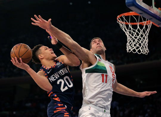 New York Knicks' Kevin Knox, left, drives to the basket past Milwaukee Bucks' Brook Lopez during the first half of the NBA basketball game, Tuesday, Dec. 25, 2018, in New York.