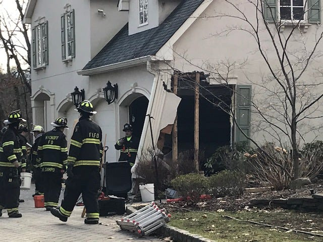 Firefighters try to repair damage caused by a car that crashed into the house Christmas morning.
