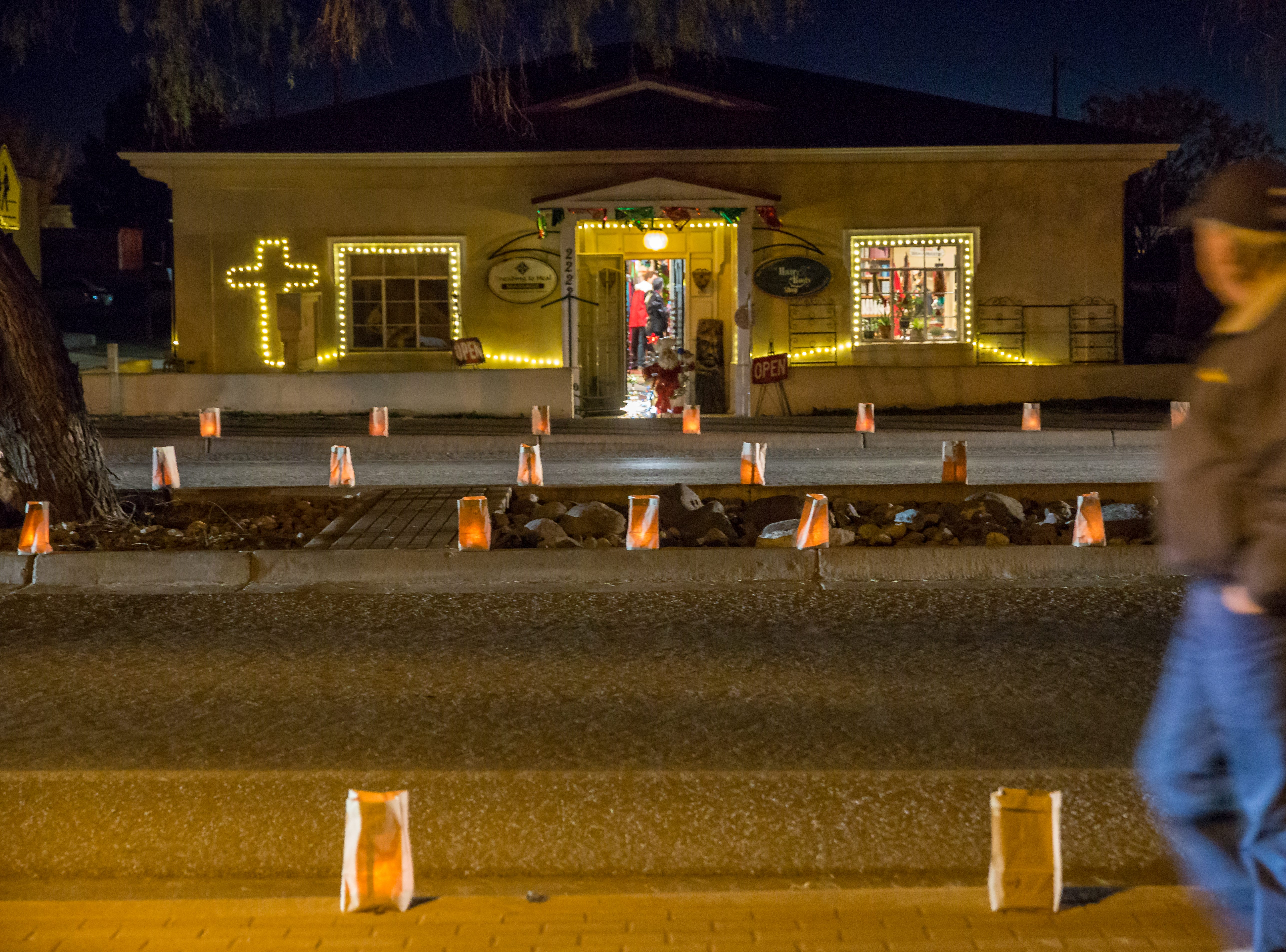 Luminarias glow in front of A Hair and Body Shop, located at 2222 Avenida de Mesilla on Monday, Dec. 24, 2018.