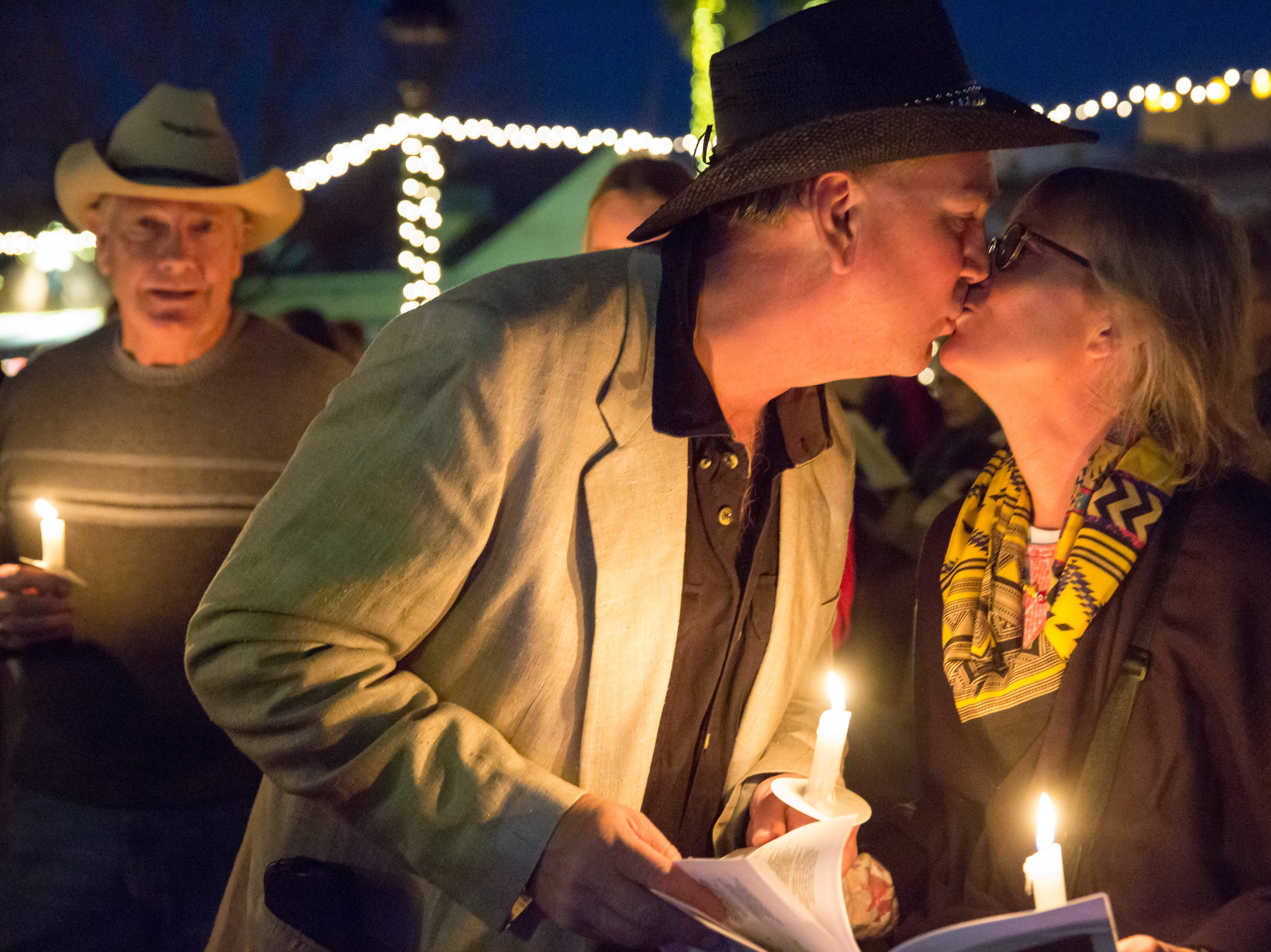 Chris Campbell, left, and Tracy Thomas, of Las Cruces, share a kiss on Monday, Dec. 24 during the caroling at the Mesilla Plaza.