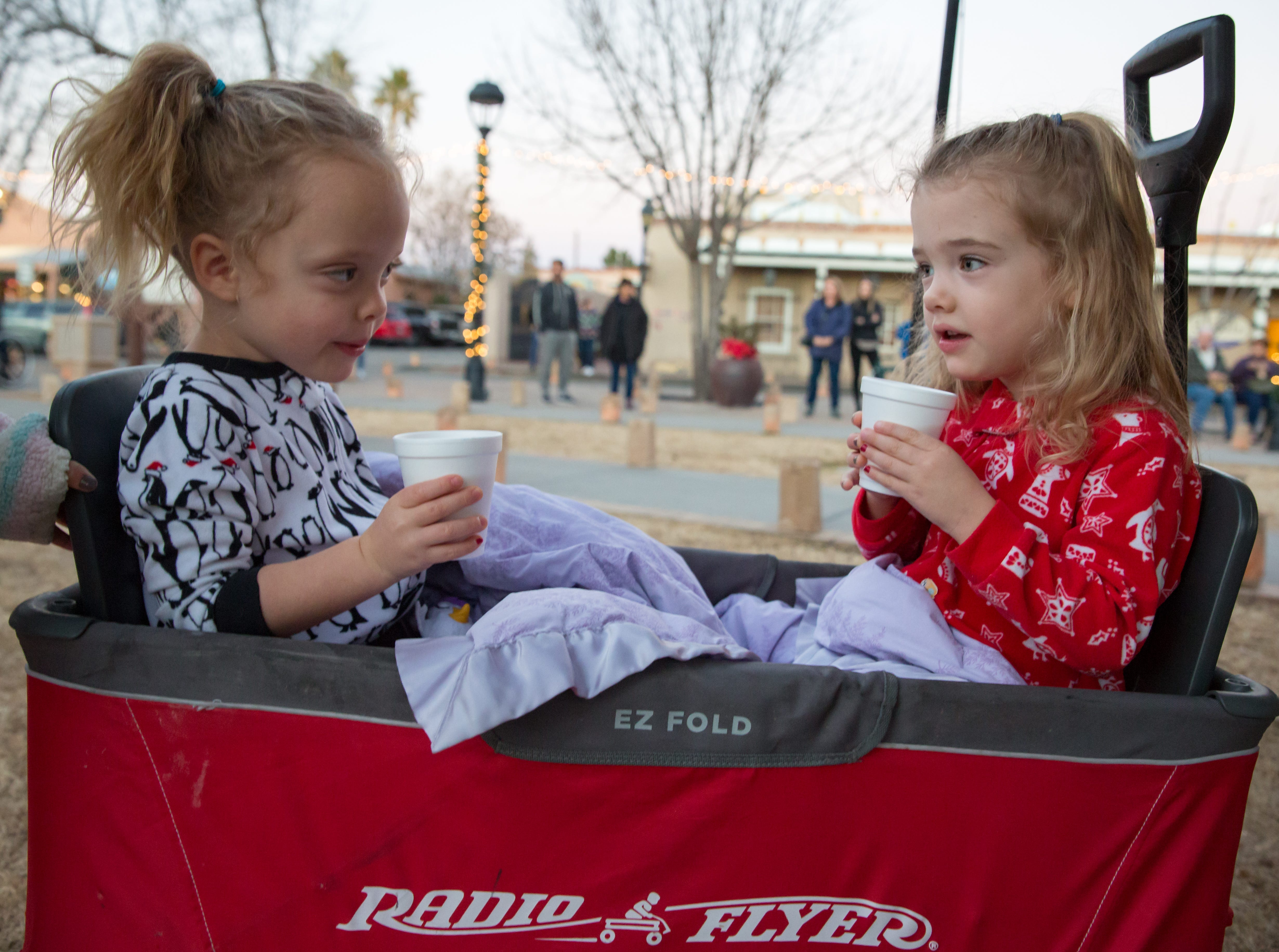 Aurora Perez, 3, right, and Zelda Perez, 3, left, drink hot cocoa at the Mesilla Plaza on Christmas Eve, Monday, Dec. 24, 2018. There were 6,000 luminarias lit by the historic village of Old Mesilla.